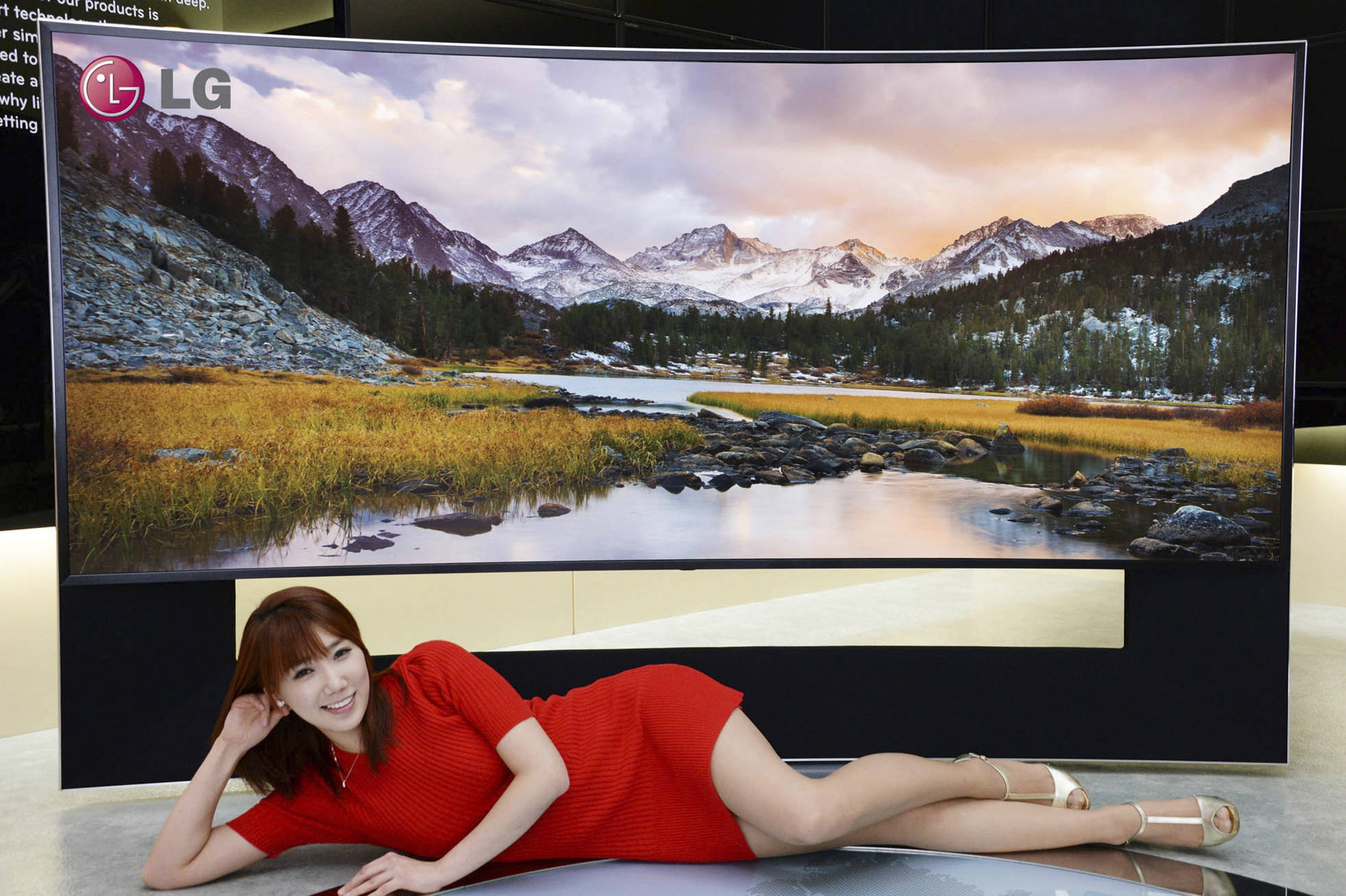 A model poses with an LG Electronics' 105-inch ultra-HD TV with a curved screen in Seoul, South Korea.