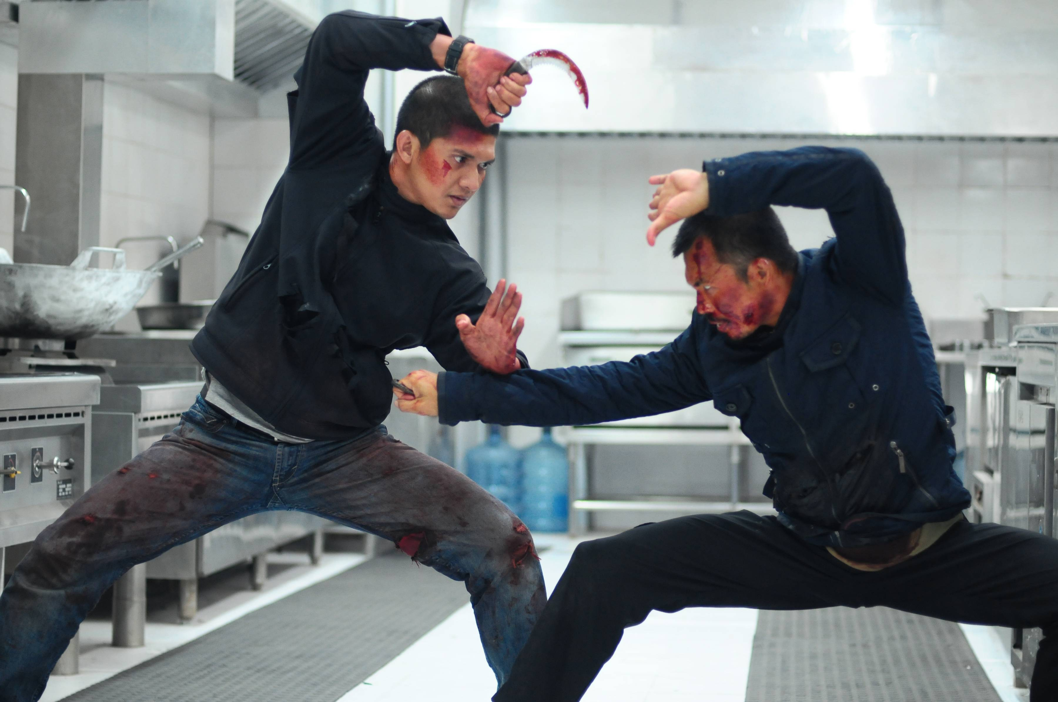 "Rama (Iko Uwais, left) fights off an assassin (Cecep Arif Rahman) in ""The Raid 2."""