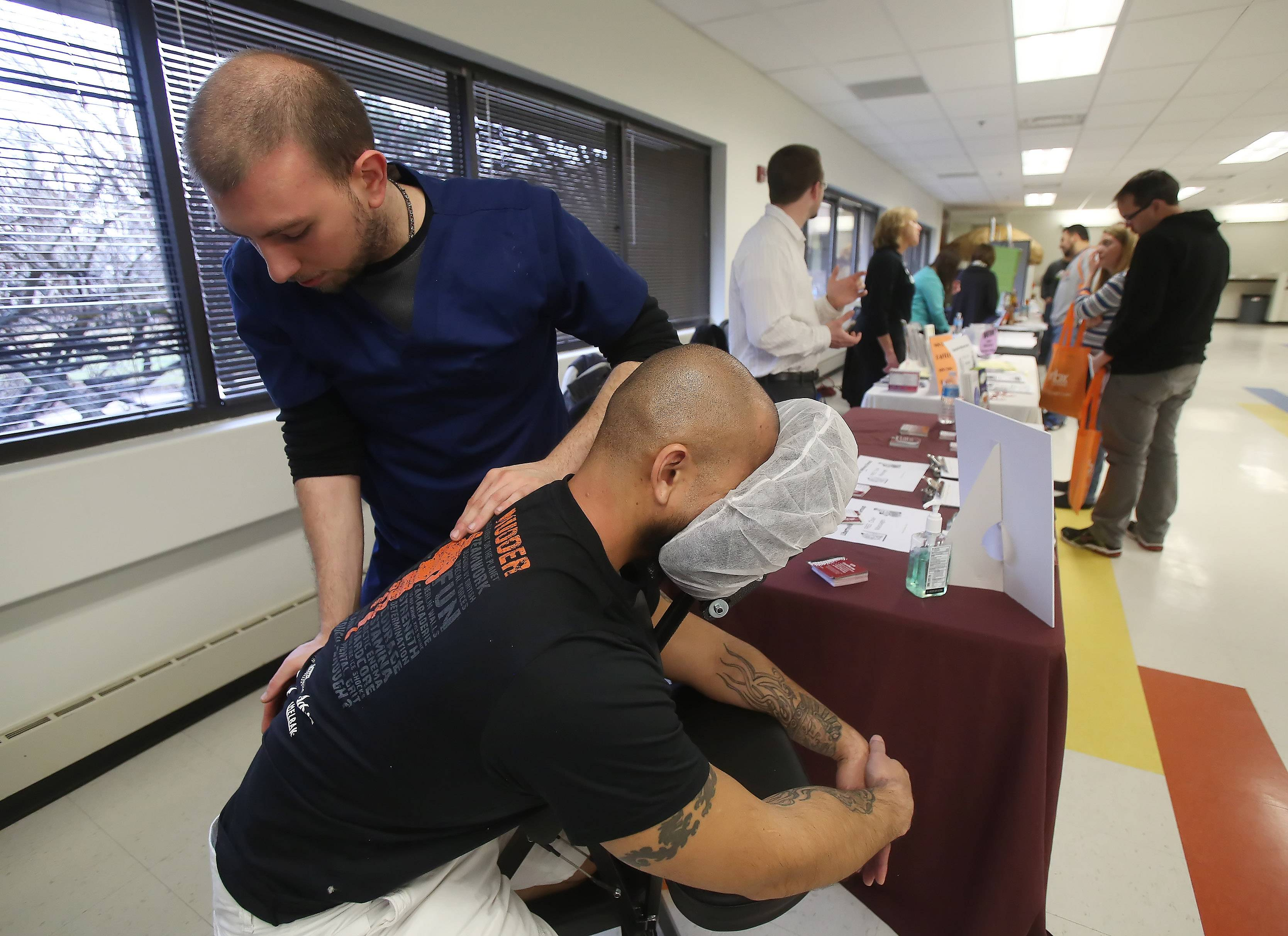 "Licensed masseuse Frank Arantopoulos, of the Libertyville Wellness Group, gives a massage to support engineer Shayne Wood during Thursday's health and wellness fair at MBX Systems in Libertyville. More than 100 employees participated in the inaugural fair with the theme ""Spring Into Wellness."""