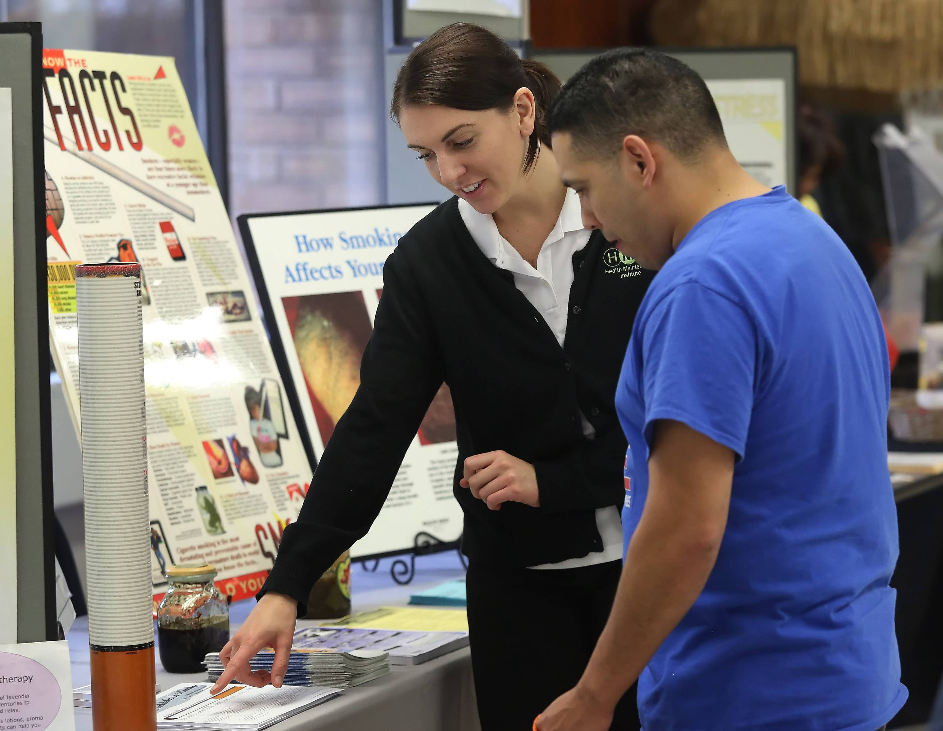 "Kathryn Robinson, health promotions coordinator for Health Maintenance Institute, discusses the dangers of smoking with assembly technician Ernesto Ramirez during Thursday's health and wellness fair at MBX Systems in Libertyville. More than 100 employees participated in the inaugural fair with the theme ""Spring Into Wellness."""