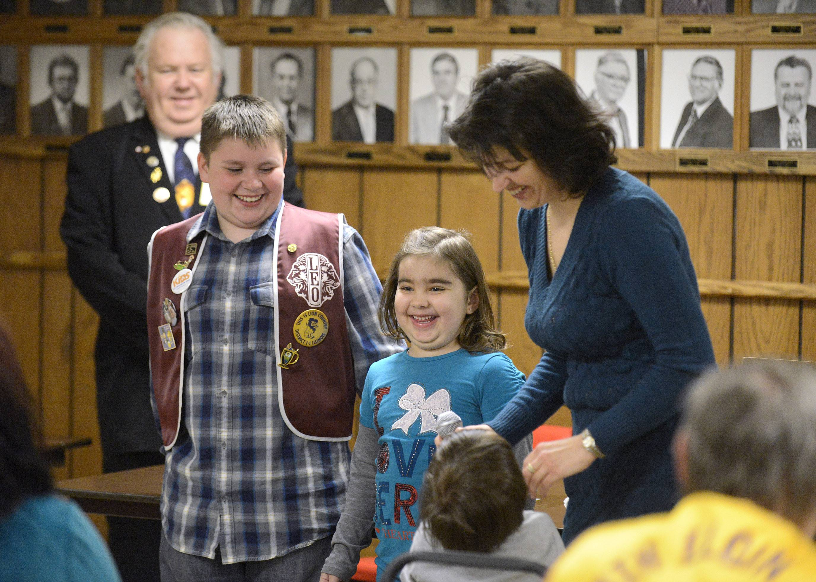 Dylan Snyder, 11, a fifth-grade student at Willard Elementary School, presents a check for nearly $4,000 to Maria Serban, 6, her mother, Elena, and brother, Victor, 3½, at the South Elgin Lions Club on Wednesday. All live in South Elgin. Maria, a first-grader at Willard, has a rare form of arthritis. Dylan raised funds to help Maria with a spaghetti dinner and auction held last month at the club where his great-grandfather Leo Snyder, standing in background, is a member.