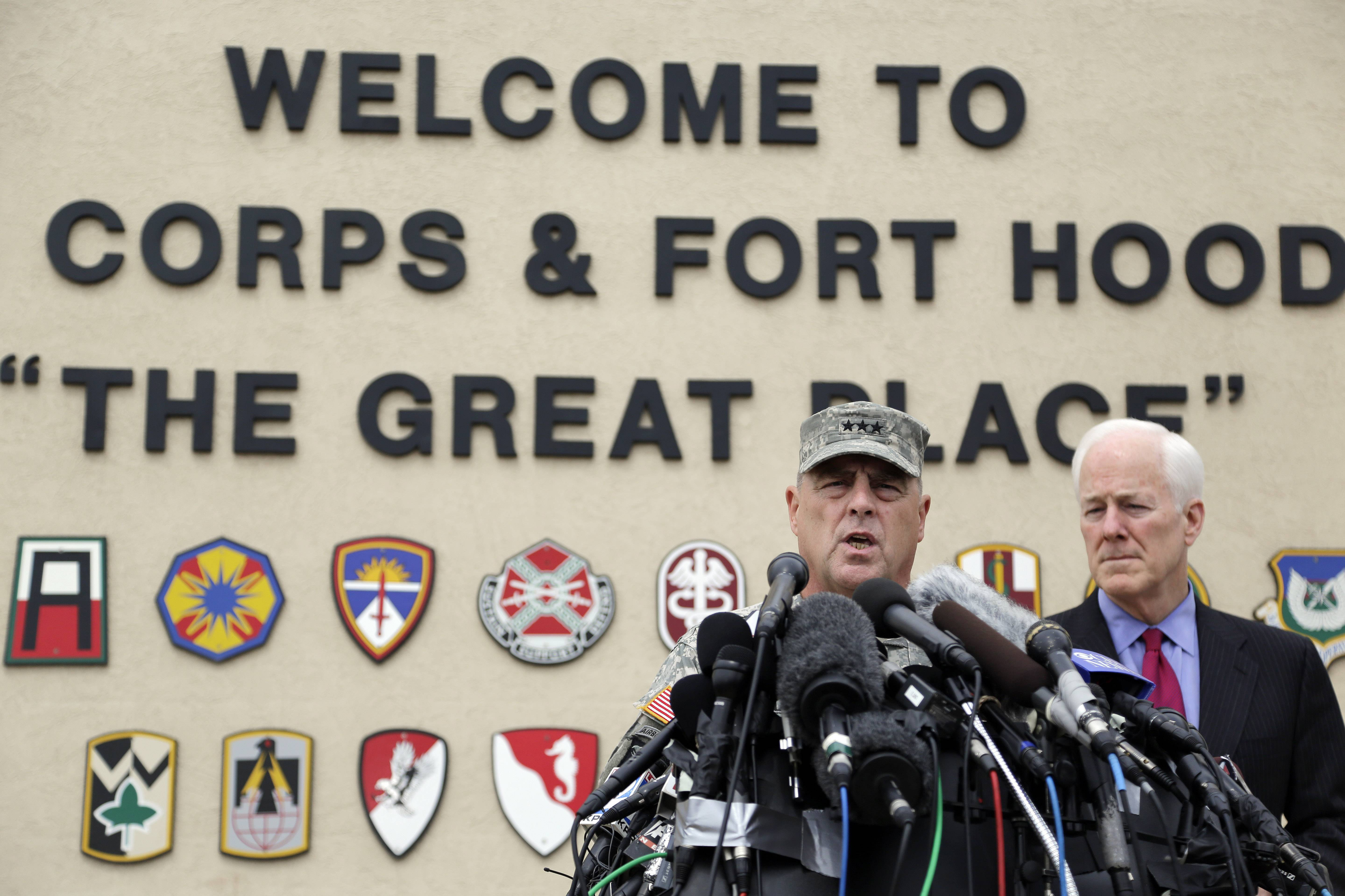 Lt. Gen. Mark Milley, left, and U.S. Sen. John Cornyn, right, talk to the media near Fort Hood's main gate Thursday. A soldier opened fire Wednesday on fellow service members at the base, killing three people and wounding 16 before committing suicide.