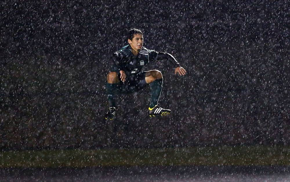 "This photo by Daily Herald photographer Steve Lundy, ""Goalie's Leap,"" was nominated for a Lisagor Award for Best Sports Photo. It shows a Grayslake Central High School soccer goalie jumping to stay warm during a game versus Antioch, which took place during a downpour."