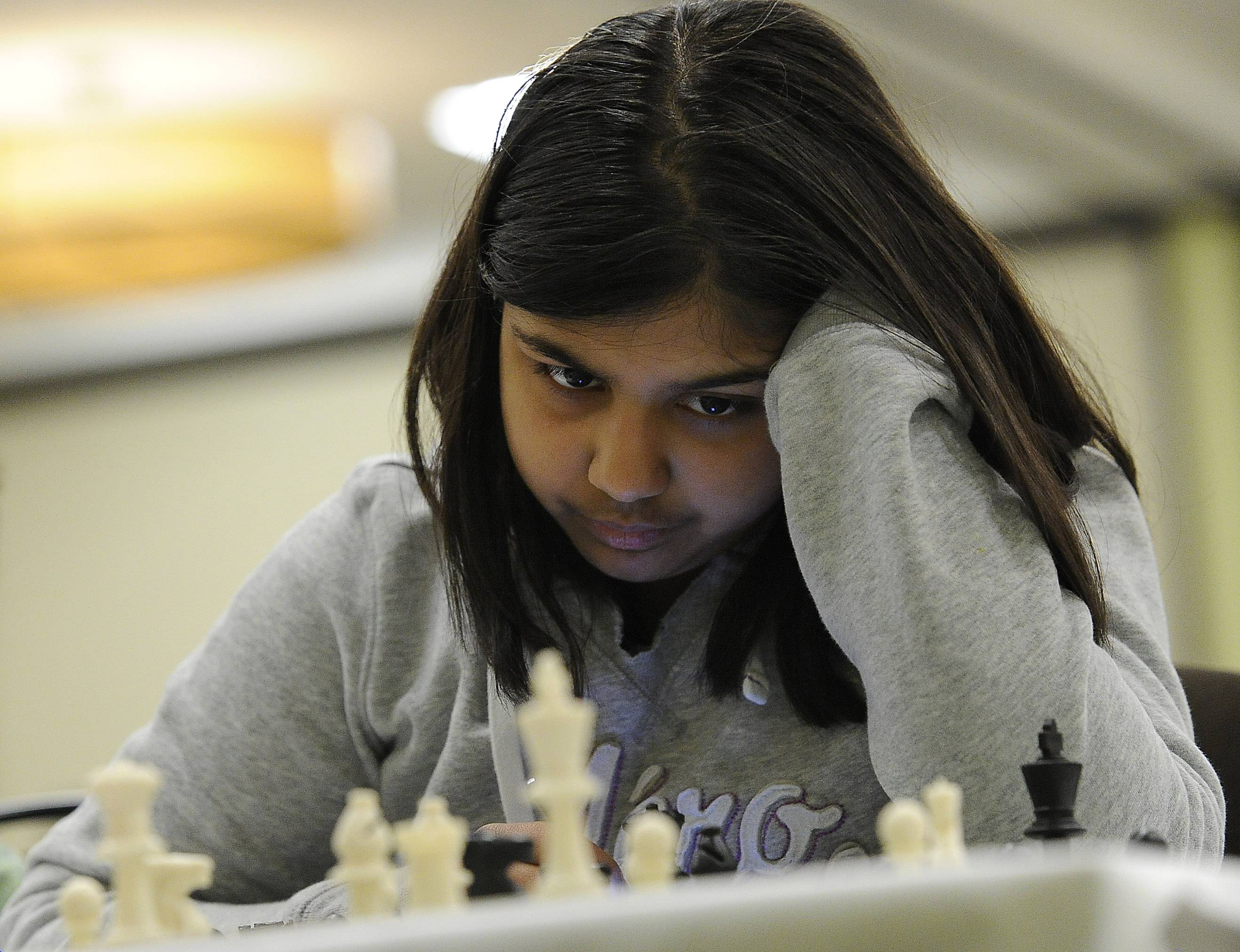 Shreya Mangalam of South Barrington studies the chessboard and moves of her opponent, Matthew Li, among the thousand or so kids that competed last month at the Illinois K-8 Chess Championships in Schaumburg.