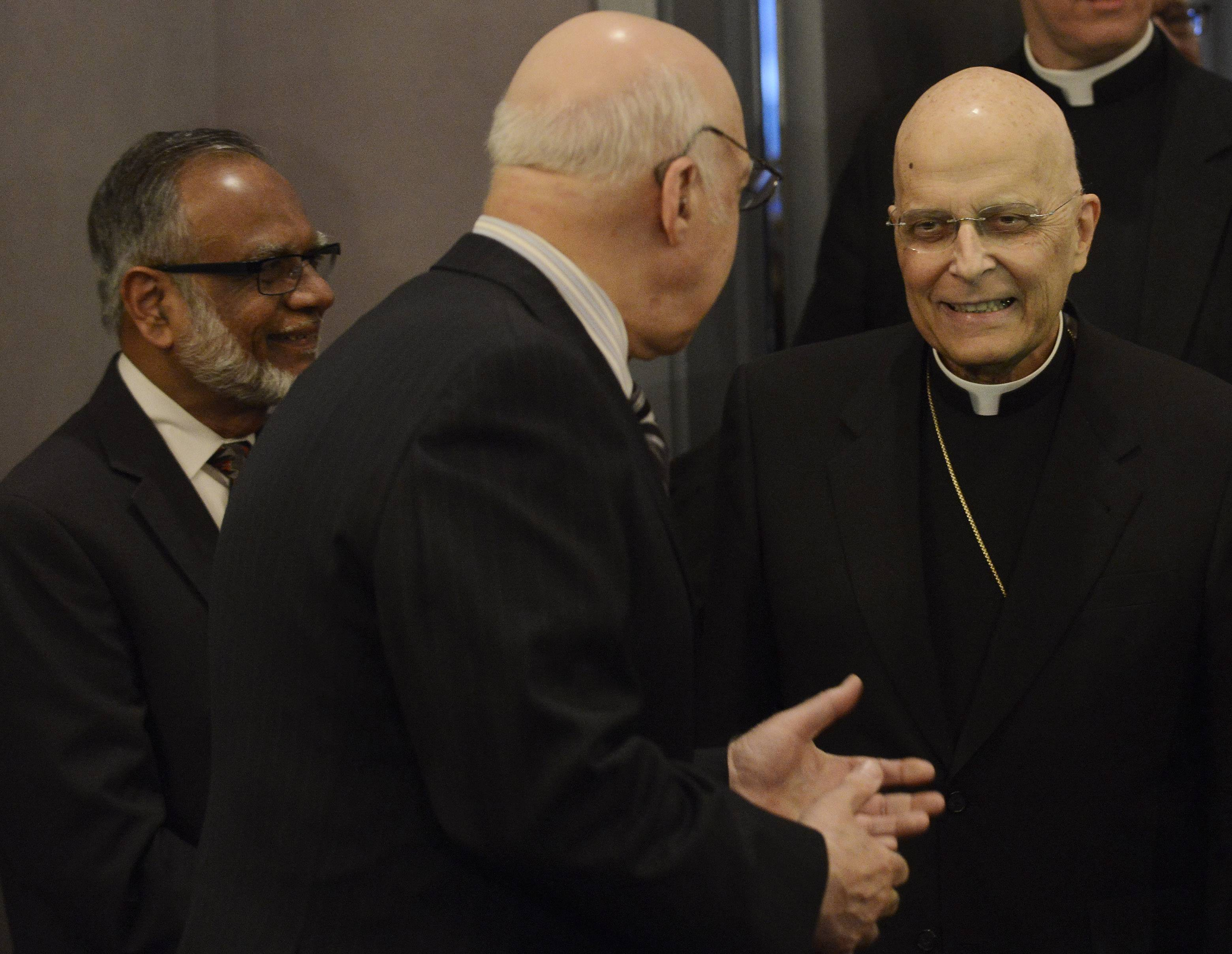 Cardinal Francis George is welcomed by Talet Othman, middle, and Mohammed Kaiseruddin to the Council of Islamic Organizations of Greater Chicago's reception in the cardinal's honor Wednesday at Rosewood Banquets in Rosemont.