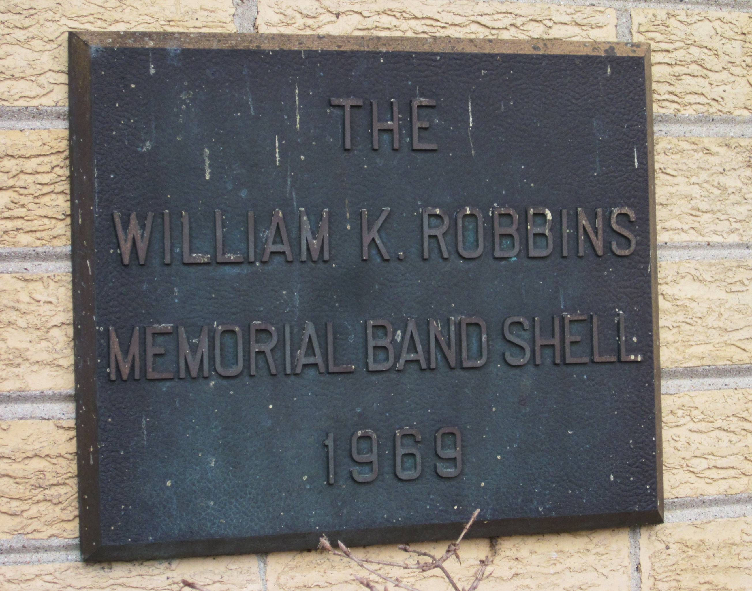 A plaque of dedication for the Butler Lake Park band shell honors a Libertyville village trustee who died in office.