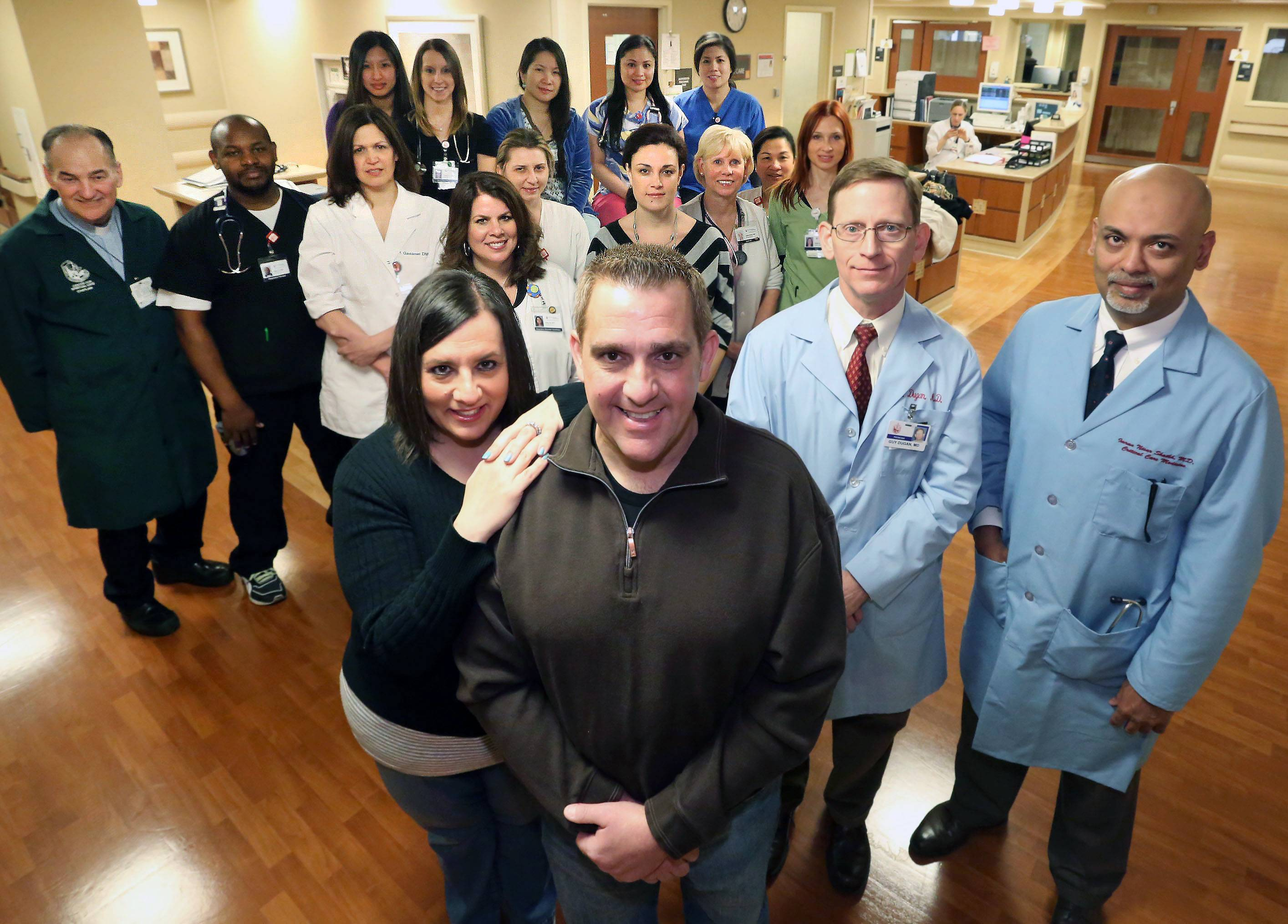 Mike LaRosa and his wife Joanna, of Schaumburg, in front, are backed by a small army of those who cared for him as he battled back from a near-deadly case of the flu at Alexian Brothers Medical Center in Elk Grove Village. Among them are doctors Guy Dugan and Imran Shaikh, left to right in blue jackets, the Rev. Bill Veith, far left, and patient care technicians, respiratory therapists, registered nurses and advanced practice nurses.