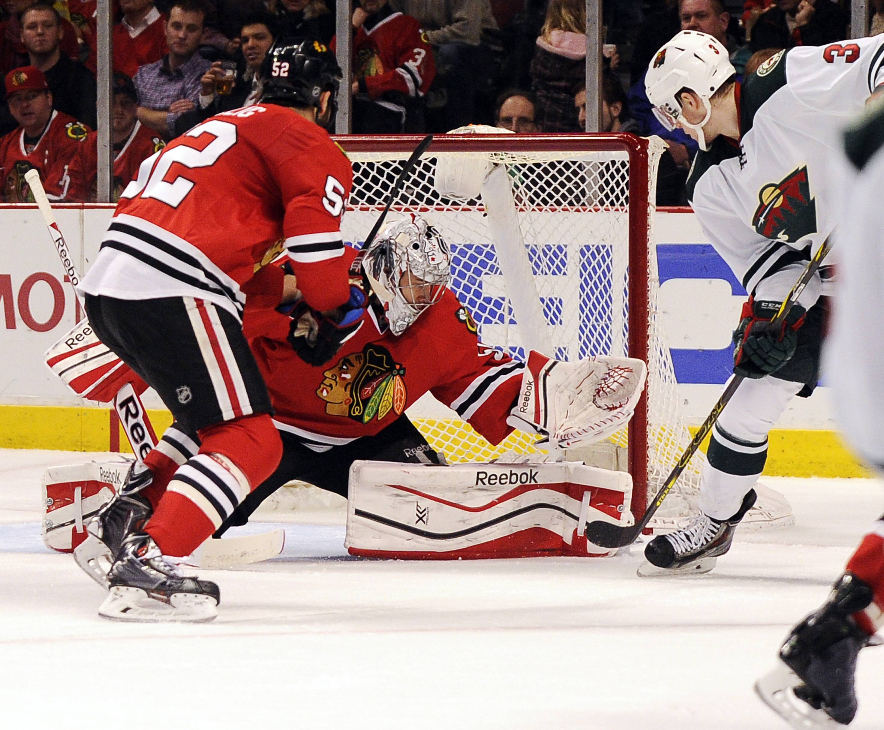 Minnesota Wild's Charlie Coyle (3) scores a goal on Chicago Blackhawks goalie Corey Crawford, center, as Brandon Bollig skates near in the first period of an NHL hockey game in Chicago, Thursday, April 3, 2014.
