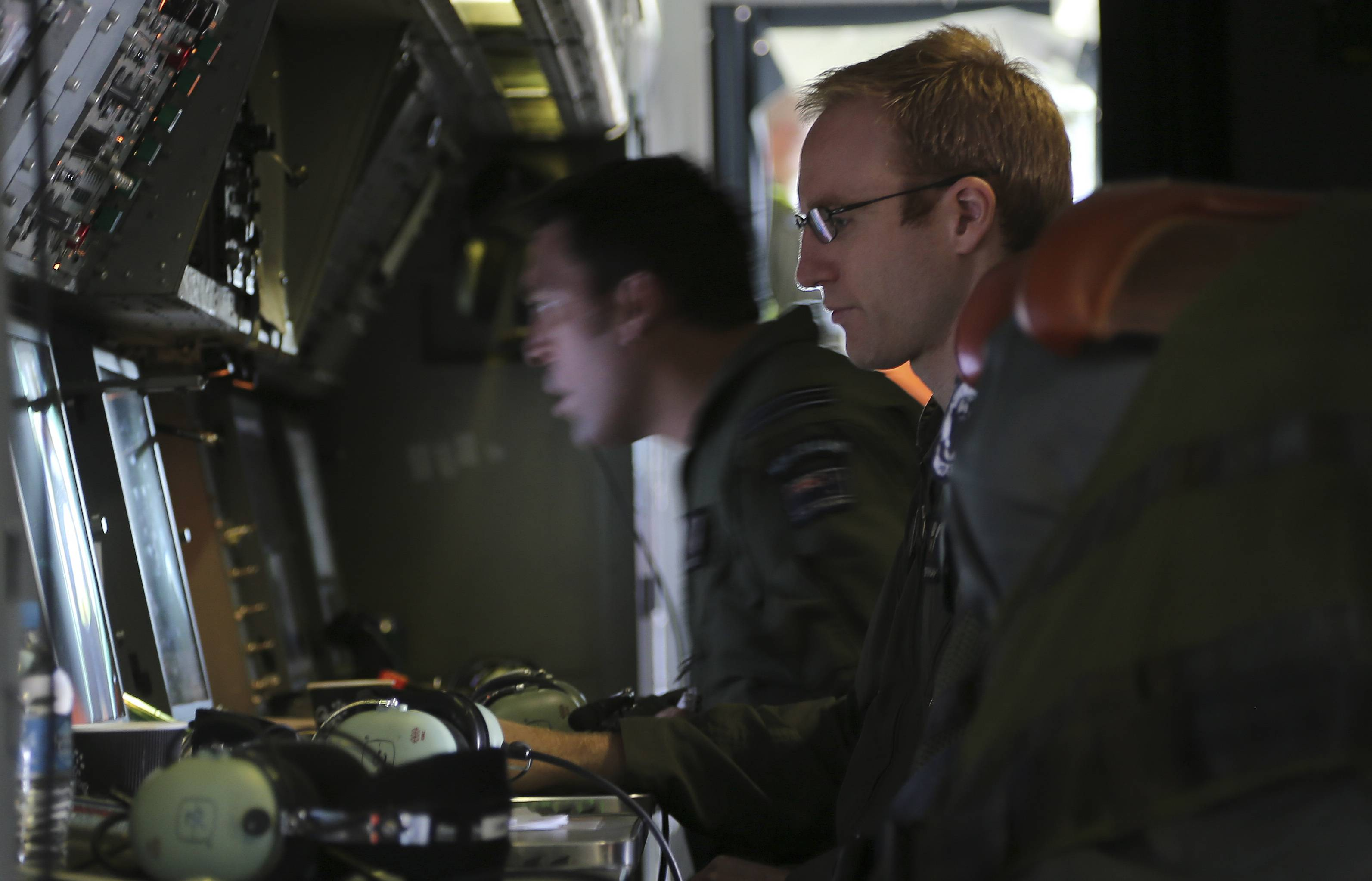 Flight Lieutenant Stephen Graham monitors a TAC station onboard a Royal New Zealand Air Force P3 Orion during search operations for wreckage and debris of missing Malaysia Airlines Flight MH370 in the southern Indian Ocean, near the coast of Western Australia, Friday, April 4, 2014. Ten military planes, four civil jets and nine ships will assist in the search today of 217,000 square kilometers, 1700kms north west of Perth.(AP Photo/Nick Perry/Pool)