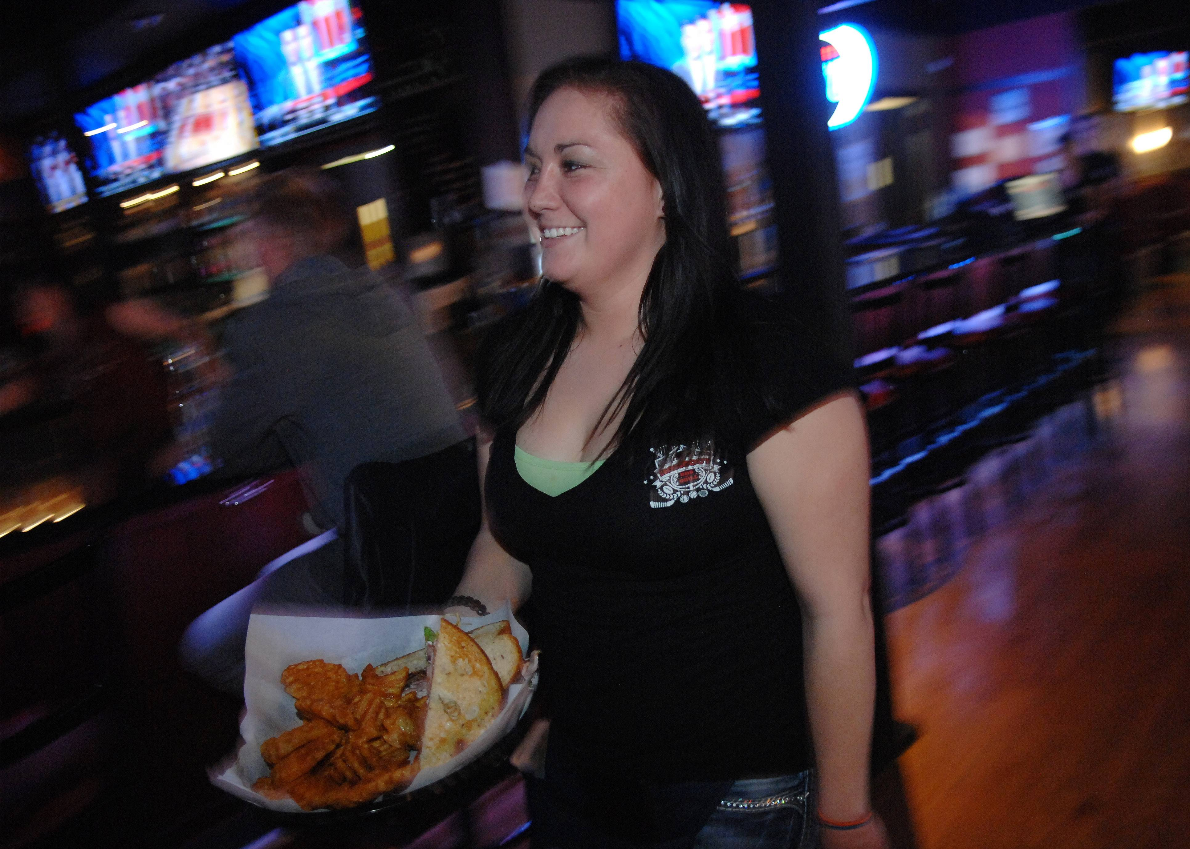 Server Stacia Harvey delivers a sandwich at D Hangout Bar and Grill in Elgin Friday.