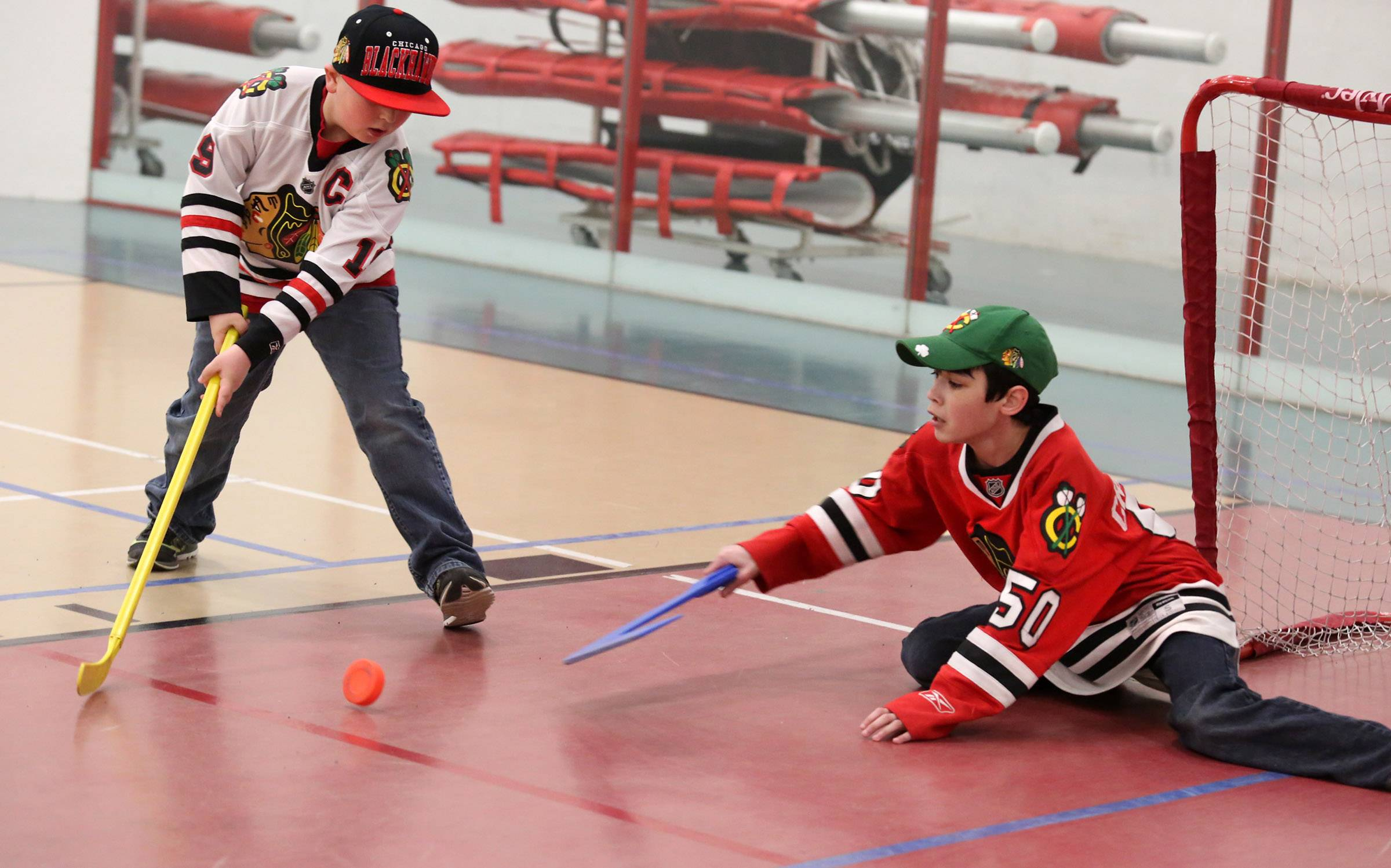 Spencer Trawin, 9, of Lindenhurst, left, takes a shot against goalie Ethan Neir, 13, of Libertyville on Friday in a practice area at the Chicago Blackhawks Roadwatch Party at the Libertyville Sports Complex.