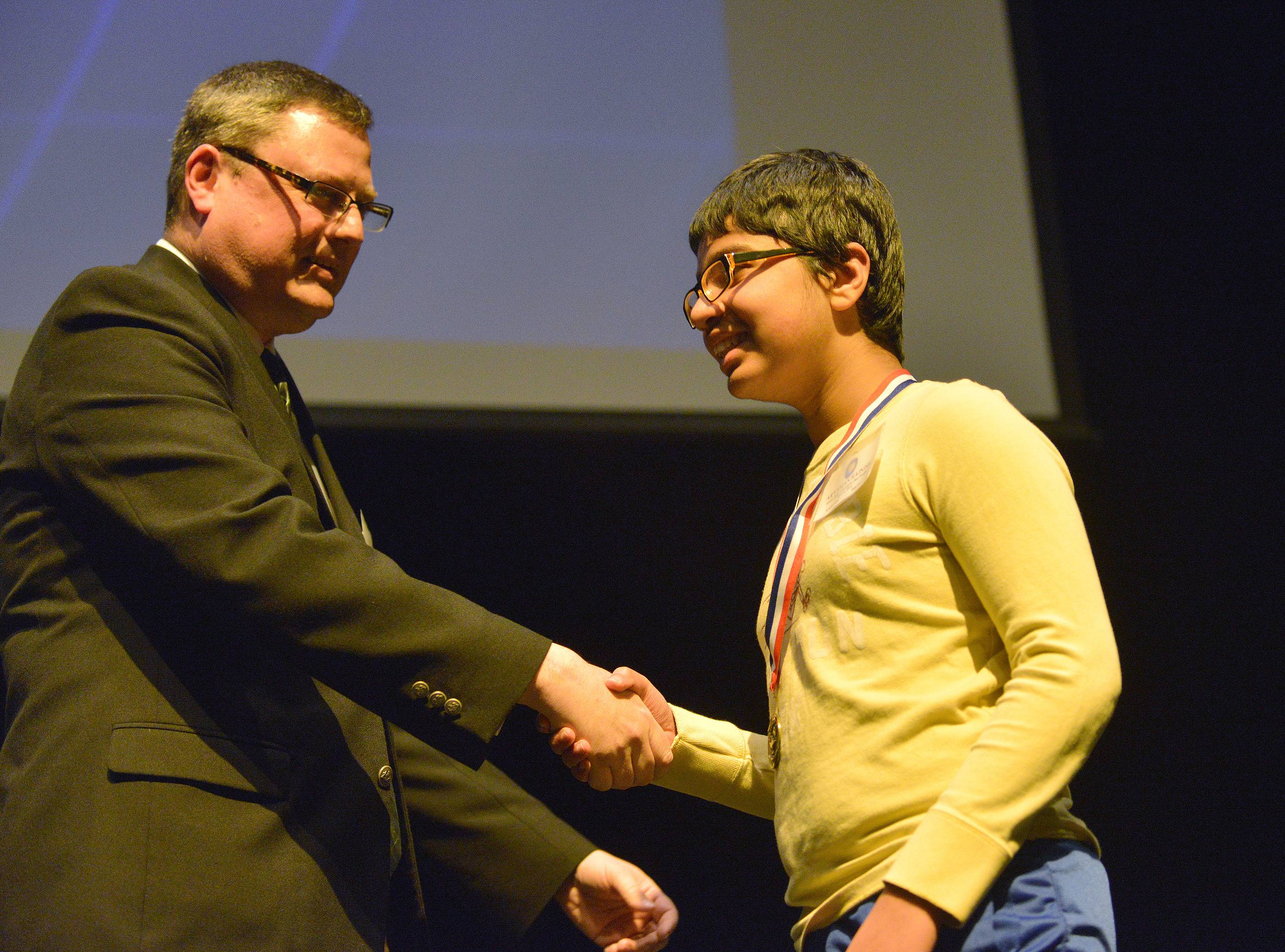 Aryaman Rajnish of Naperville receives a medal from State Coordinator Michael Middleton after competing in the state-level competition of the National Geographic Bee in Glen Ellyn Friday.