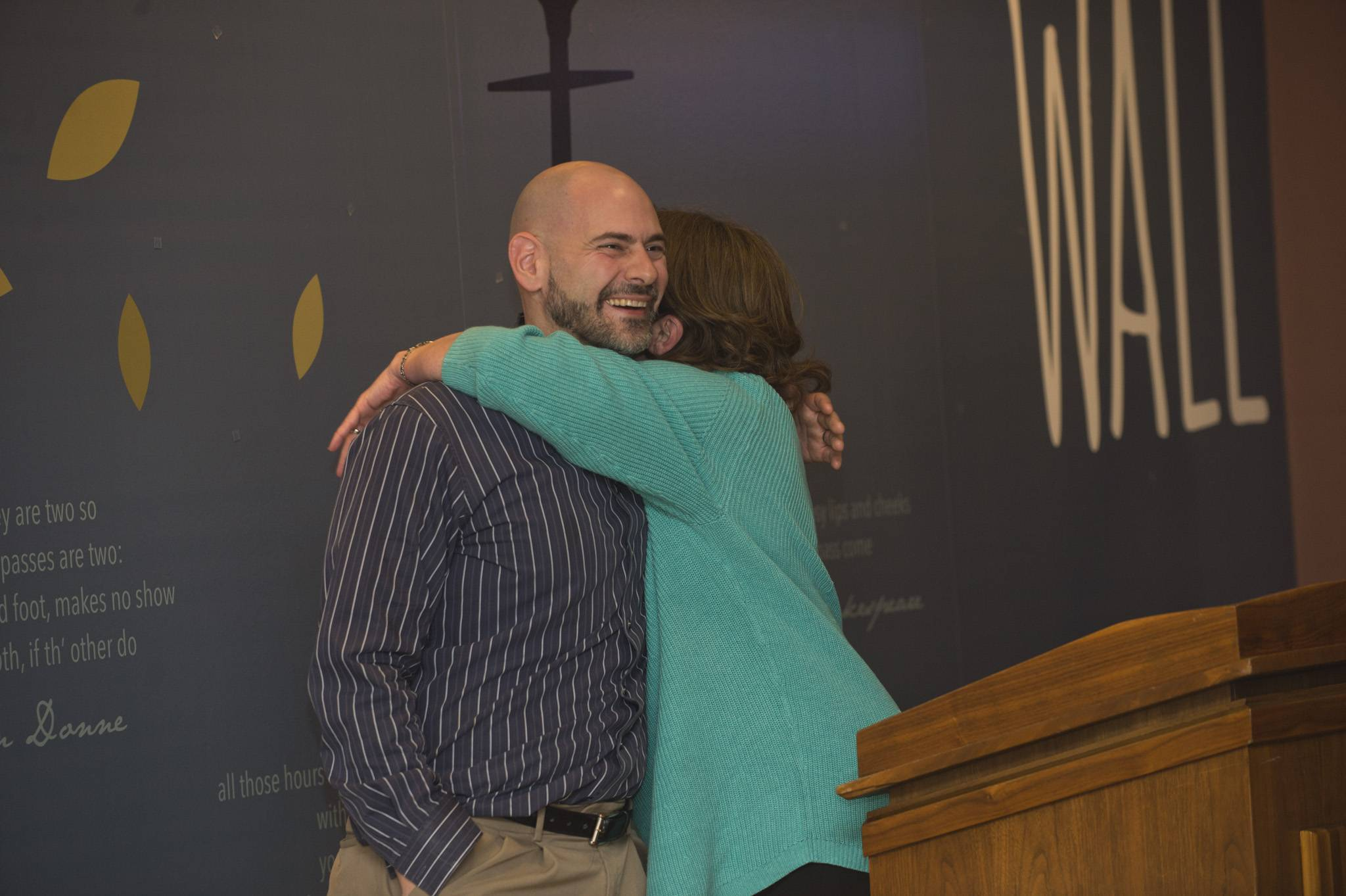 Jason Conglis, who created the graphics for the poetry wall, gets a hug from Rachael Stewart, an associate professor of English at Elgin Community College, during Thursday's event that honored former teacher Florence B. Palmer.