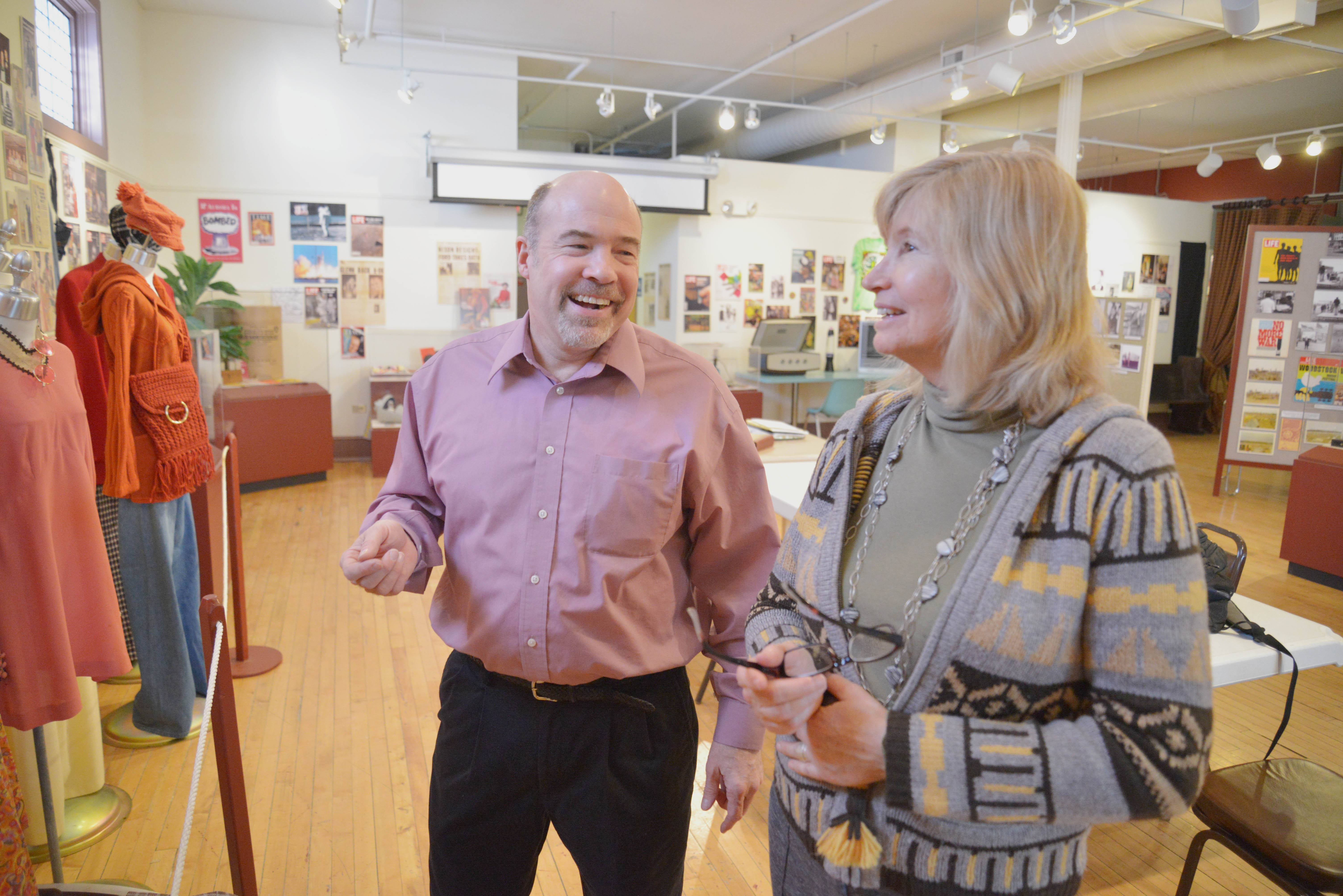 John Jaros, executive director of the Aurora Historical Society, chats with Laura Nicholson-Tom of Aurora about fashion styles of years past. This is one of the many exhibits on display at the museum.