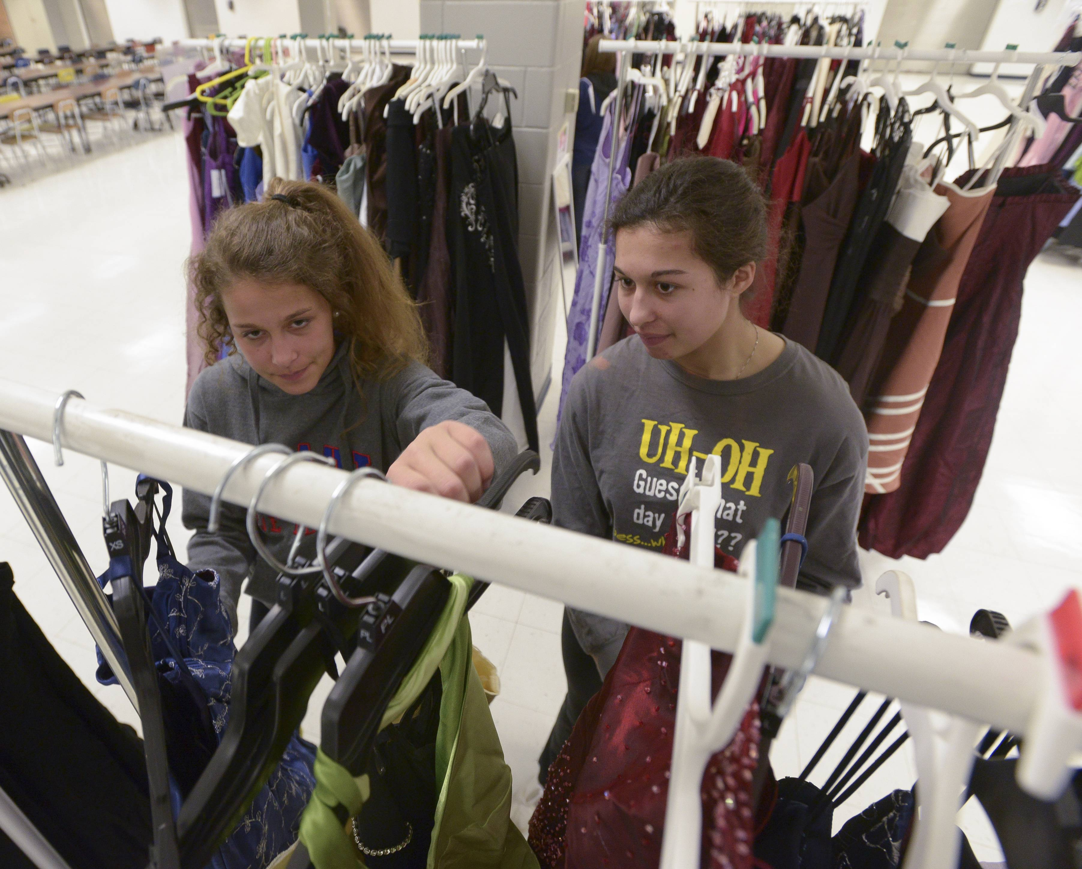 "St. Charles North sisters Elizabeth, 16 and Victoria Parrilli, 17 search for prom dresses they likes during the ""Prom Goes Green"" event sponsored by USagain at West Chicago Community High School. The event allows girls to get free prom dresses to offset the high cost of going to prom."