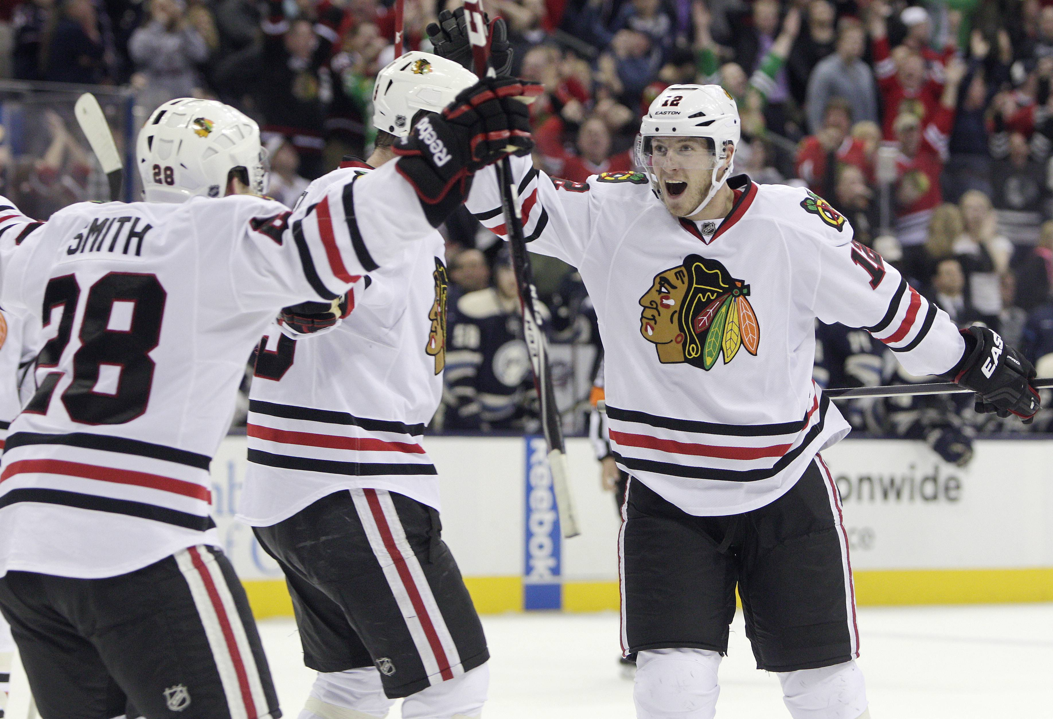 Chicago Blackhawks' Peter Regin, right, of Denmark, celebrates their goal against the Columbus Blue Jackets with teammates Ben Smith, left, and Bryan Bickell during the third period of an NHL hockey game on Friday, April 4, 2014, in Columbus, Ohio. The Blackhawks defeated the Blue Jackets 4-3.