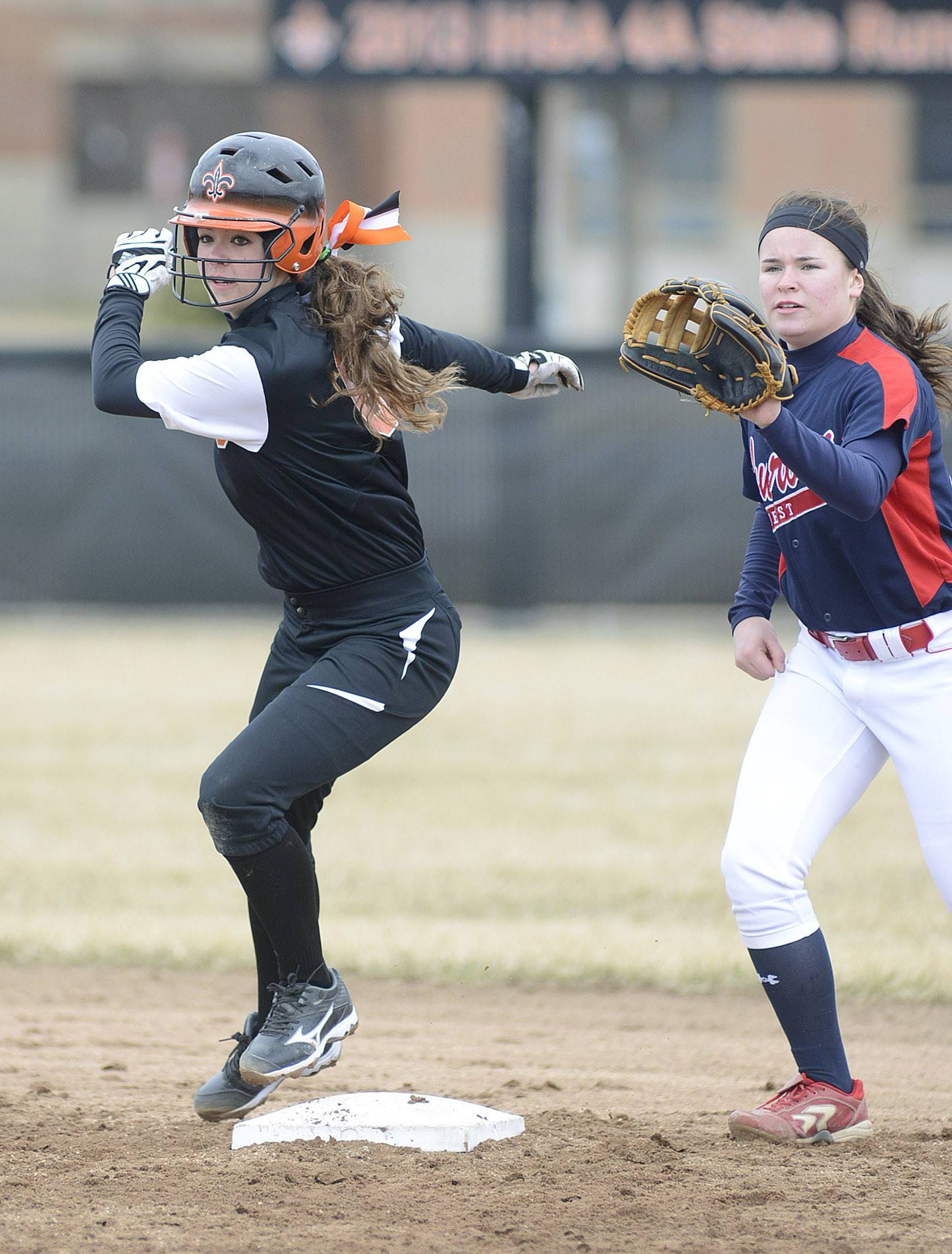 St. Charles East's Olivia Cheatham leaps safety onto second base before West Aurora's Taylor Podschweit can get the ball in her mitt in the fifth inning on Friday, April 4. Cheatham would score a run for the Saints within a few minutes.