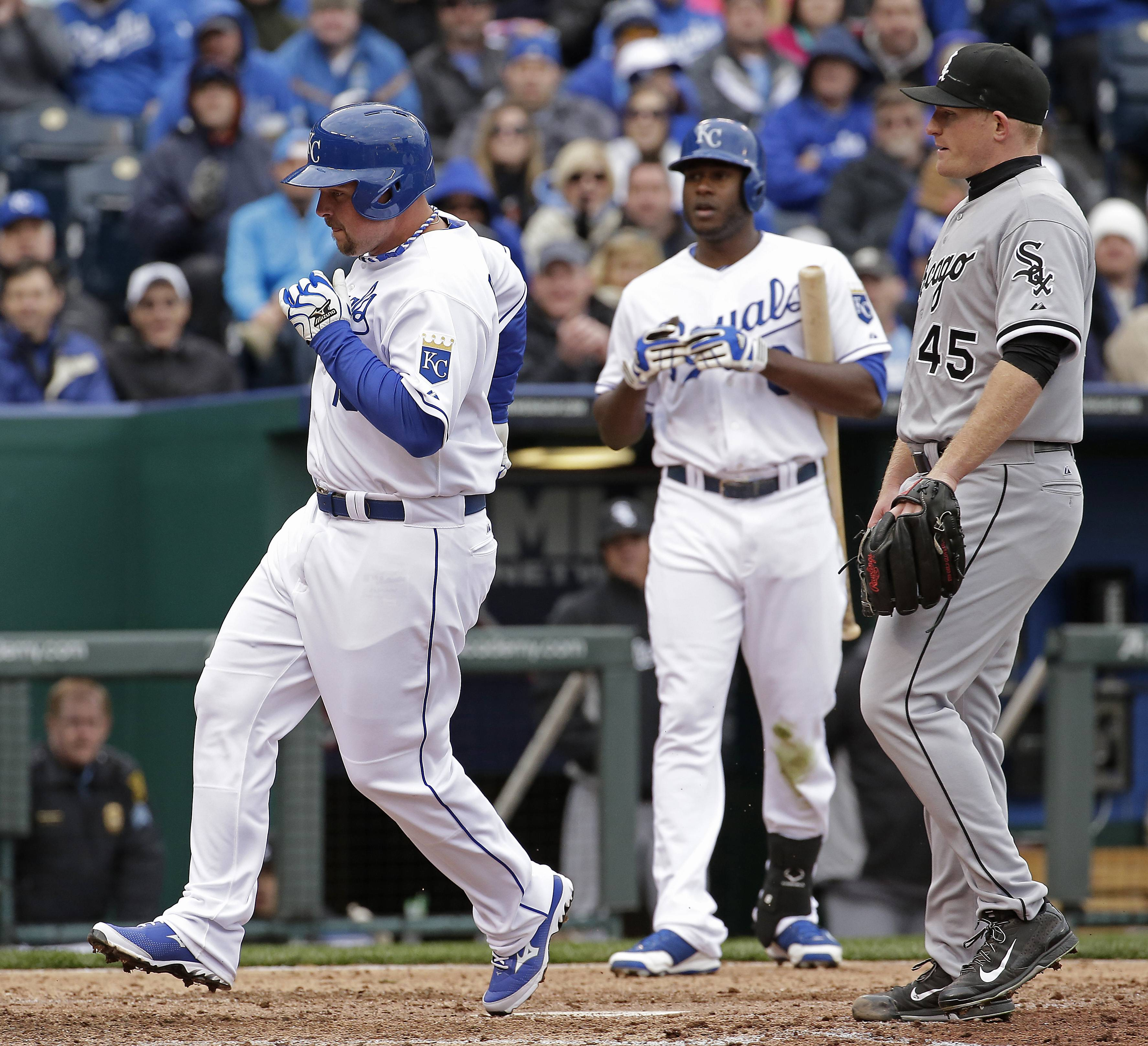 Kansas City Royals' Billy Butler, left, scores on a wild pitch thrown by White Sox pitcher Erik Johnson (45) during the fifth inning of Friday's home opener in Kansas City, Mo.