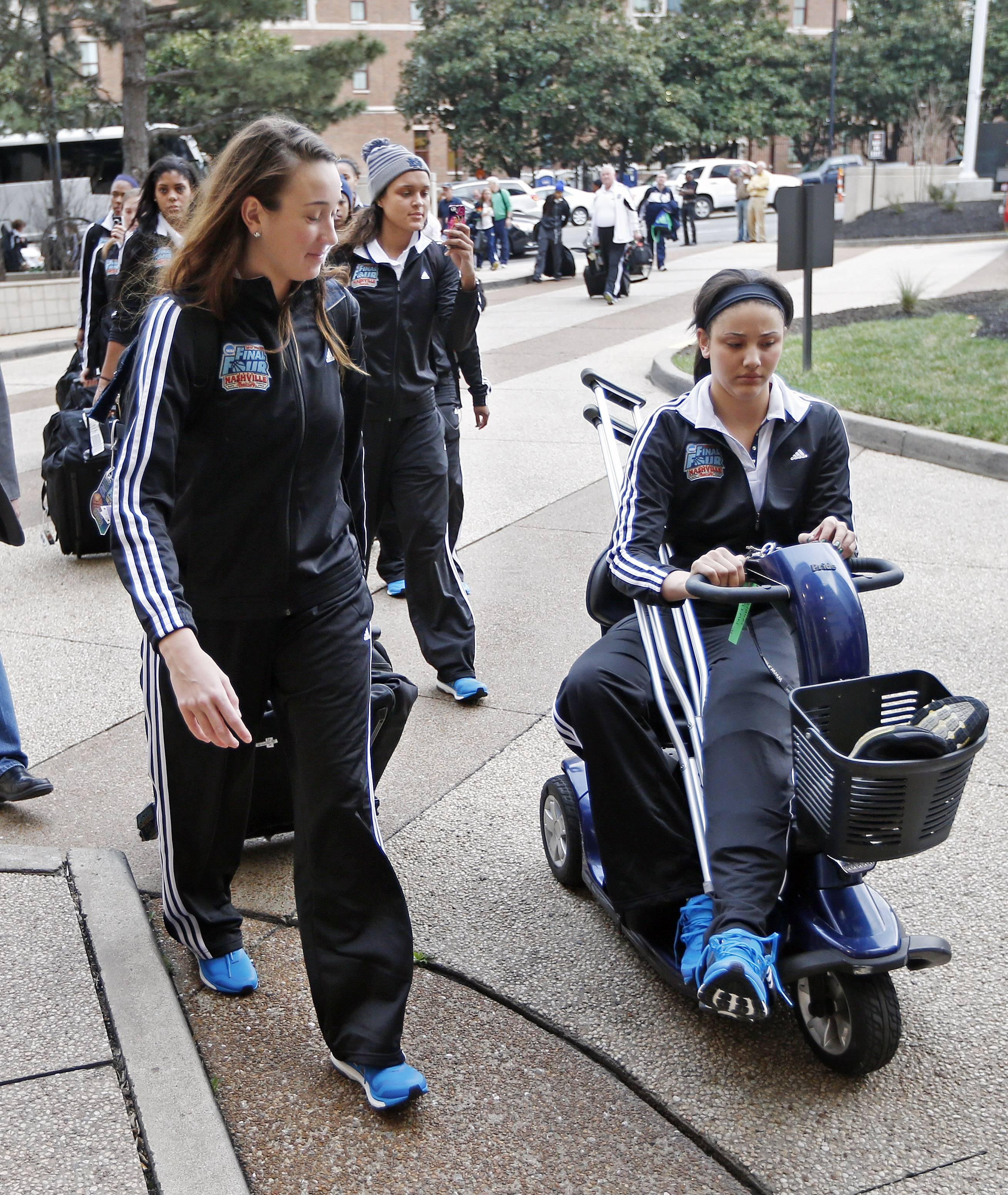 Notre Dame injured forward Natalie Achonwa, right, arrives with teammates for the NCAA women's Final Four.