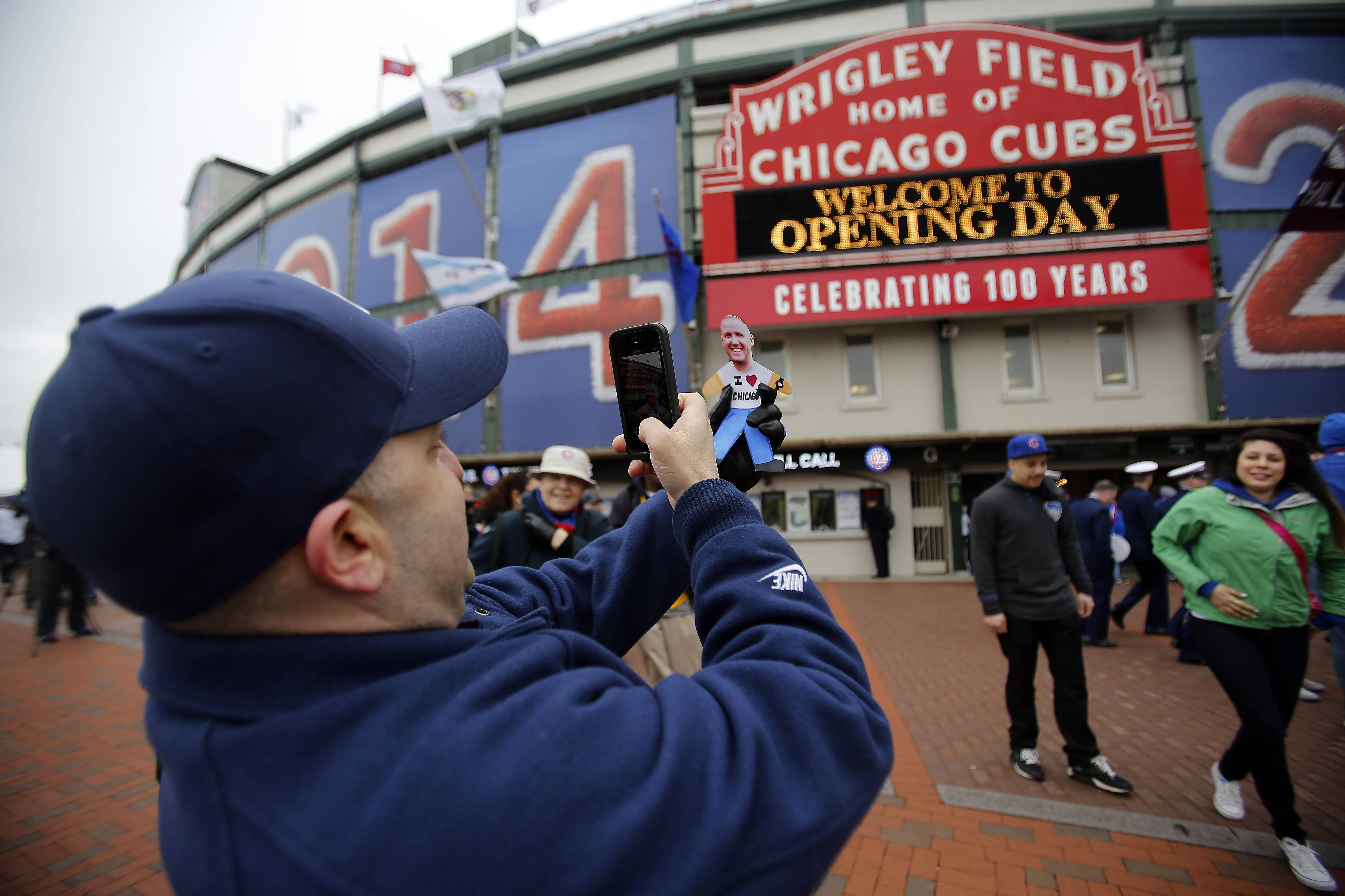 Brian Hill/bhill@dailyherald.comMark Maroon of Aurora, takes a picture of his brother-in-law Ross Fisette, Flat Stanley style before the Chicago Cubs opening day game against Philadephia Phillies Friday April 4, 2014, at Wrigley Field in Chicago. Fisette will be retiring from the Air Force this year and his family was getting pictures of his Flat Stanley style picture all over the place.