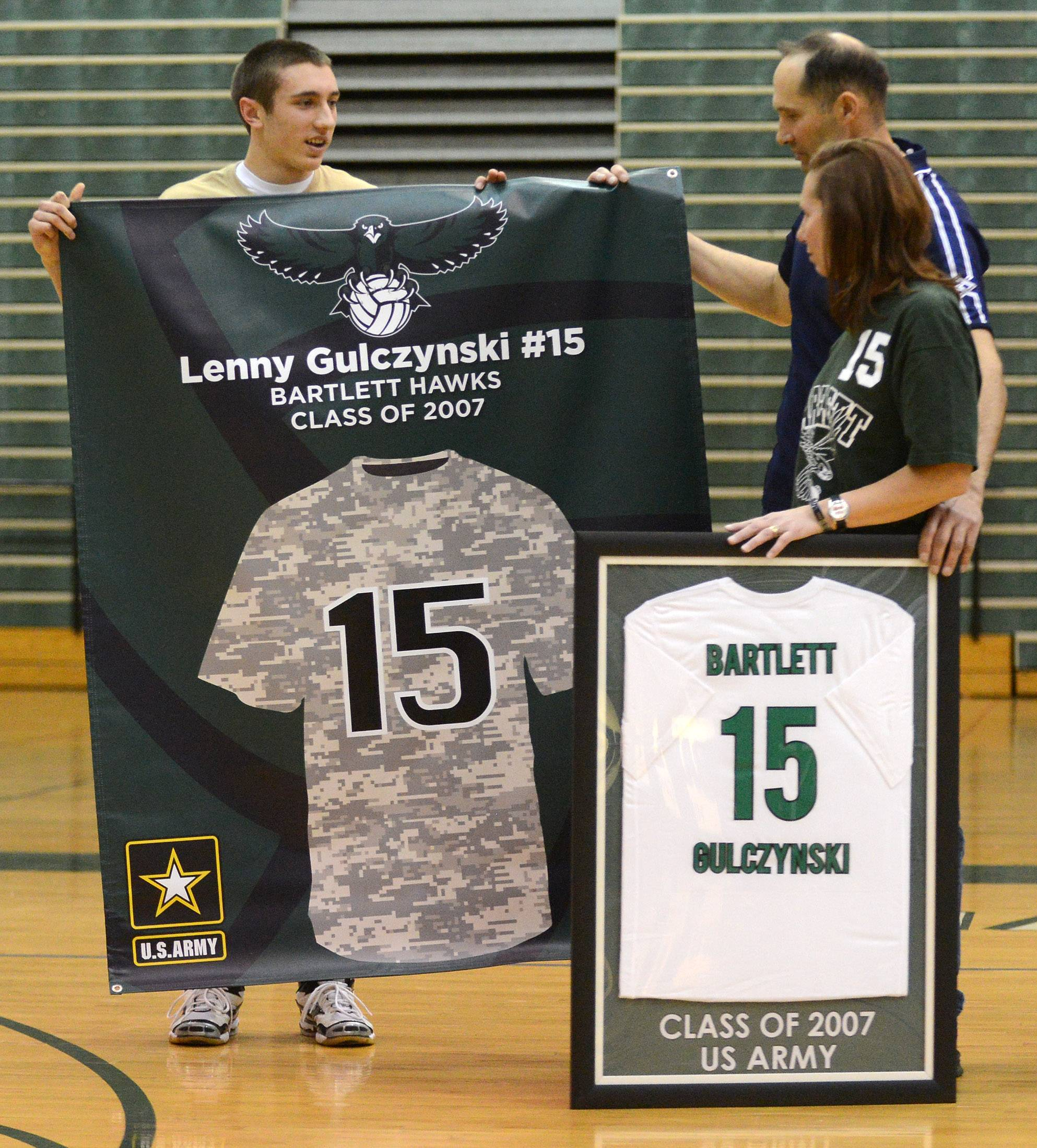 Mike Gulczynski and his parents, Mike Sr., and Jackie, admire the banner created for the jersey retirement ceremony of Mike's brother Lenny Thursday at Bartlett High School. Lenny was a 2007 grad who died while serving in Iraq.