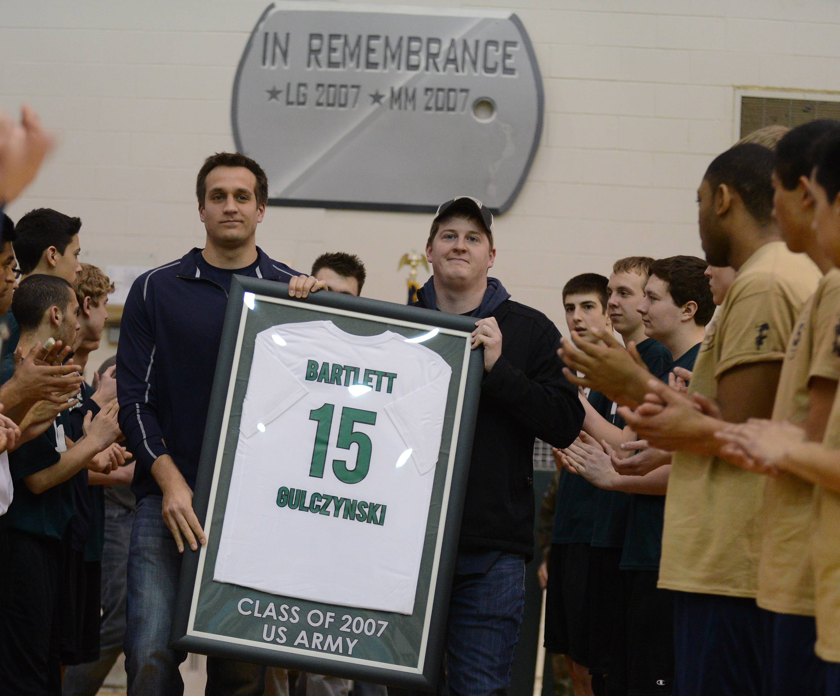 Former Bartlett High volleyball teammates Billy Sahagian, left, and Chris Maloney carry out the retired #15 jersey Thursday of Lenny Gulczynski, a 2007 grad who died while serving in the Army in Iraq in 2008.