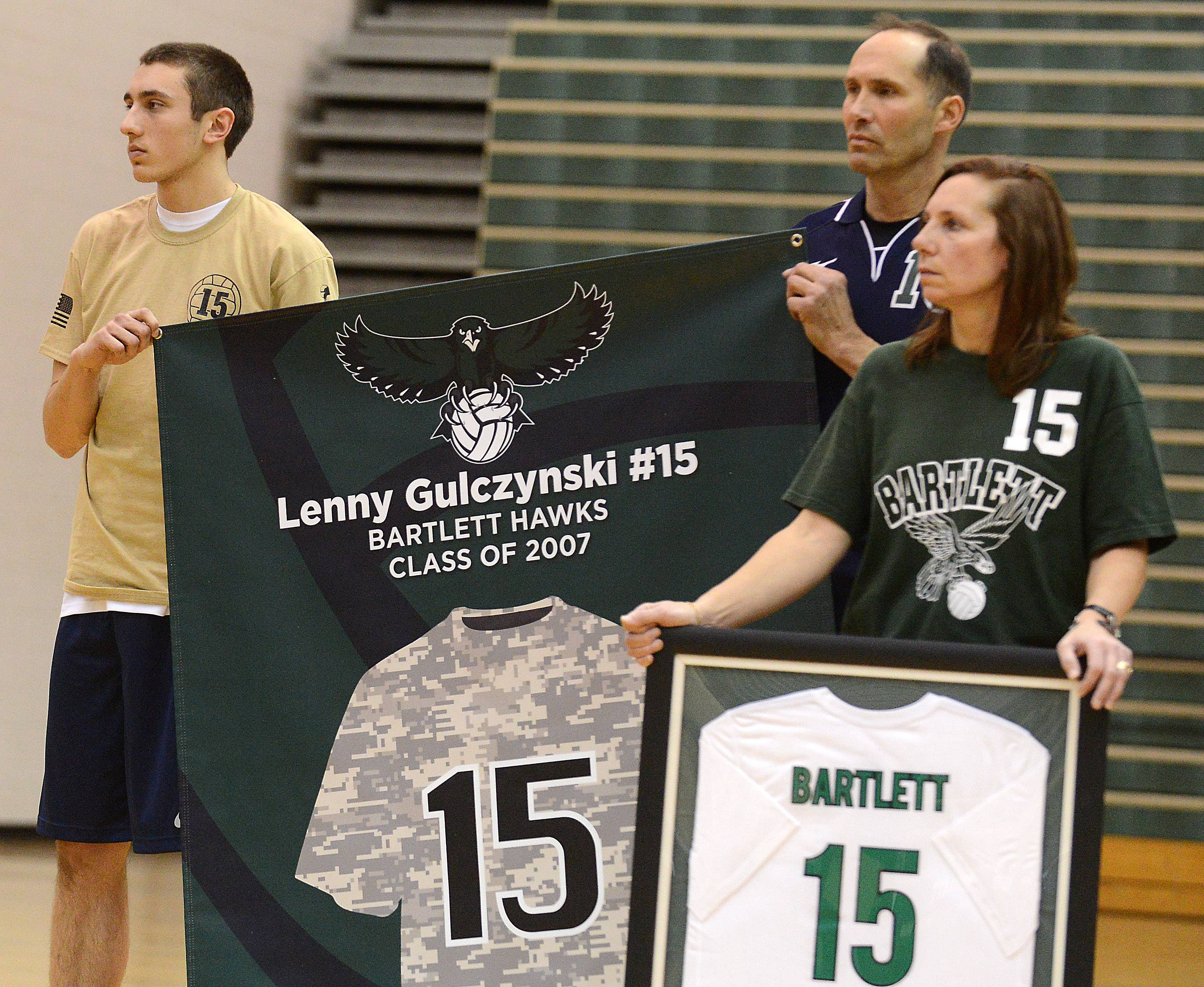 Mike Gulczynski and his parents, Mike Sr., and Jackie, listen as Taps is played during the jersey retirement ceremony for Mike's brother Lenny Thursday at Bartlett High School. Lenny was a 2007 grad who died while serving in Iraq.