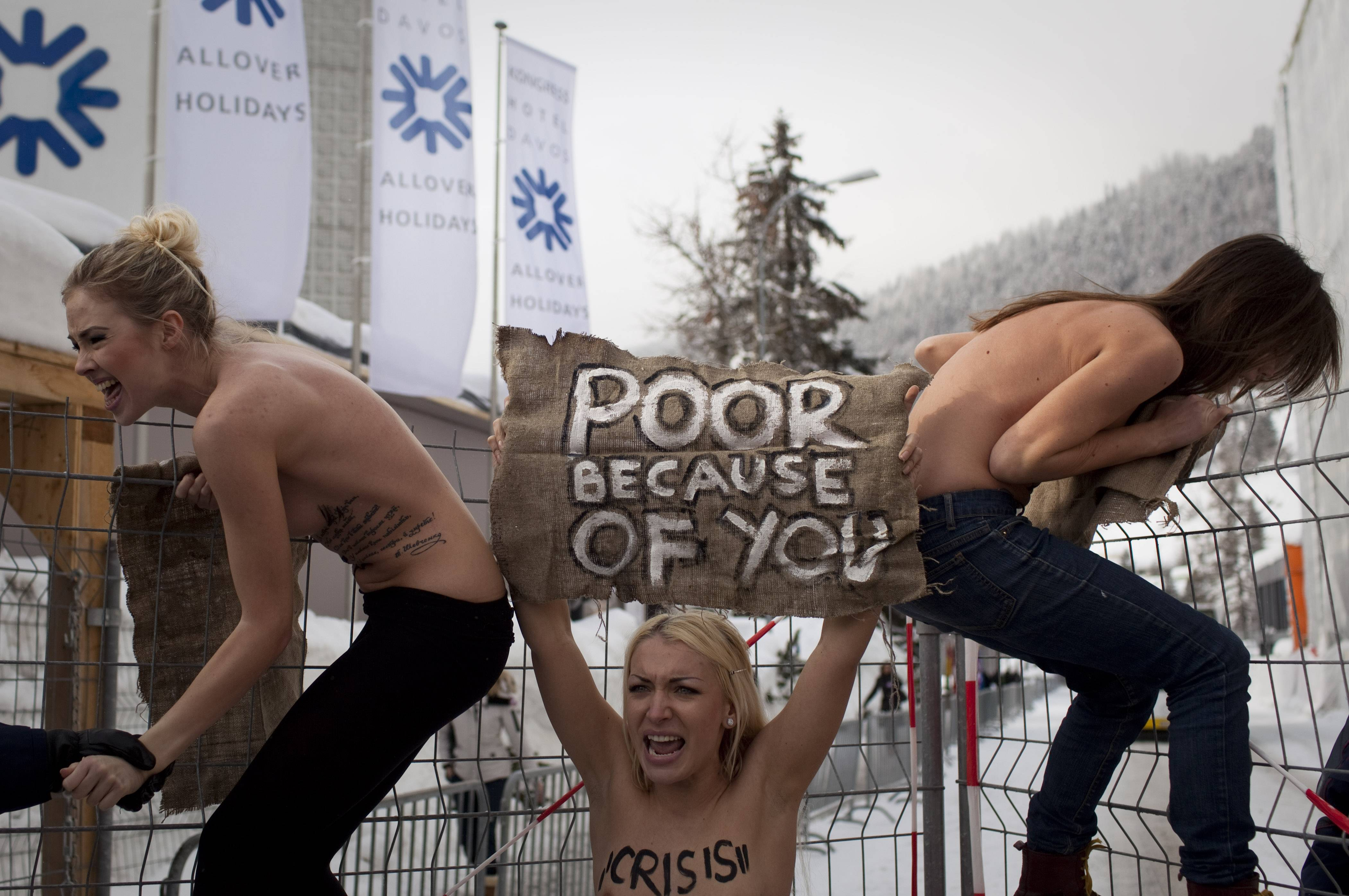 In this Saturday, Jan. 28, 2012 ile photo made by Associated Press photographer Anja Niedringhaus, topless Ukrainian protesters climb up a fence at the entrance to the congress center where the World Economic Forum takes place in Davos, Switzerland.