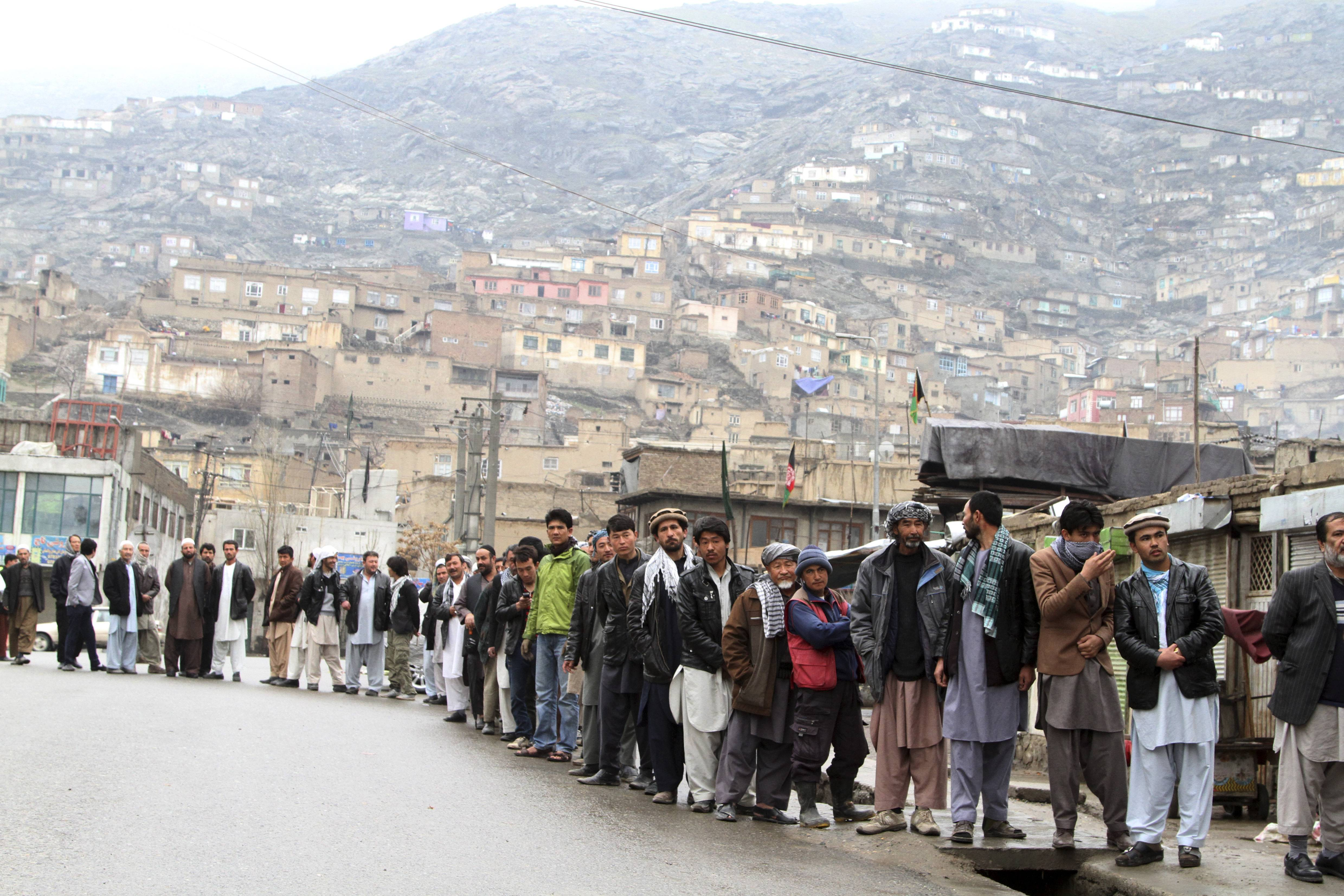 Afghan men line up outside a polling station to cast their ballots, in Kabul, Afghanistan, Saturday.