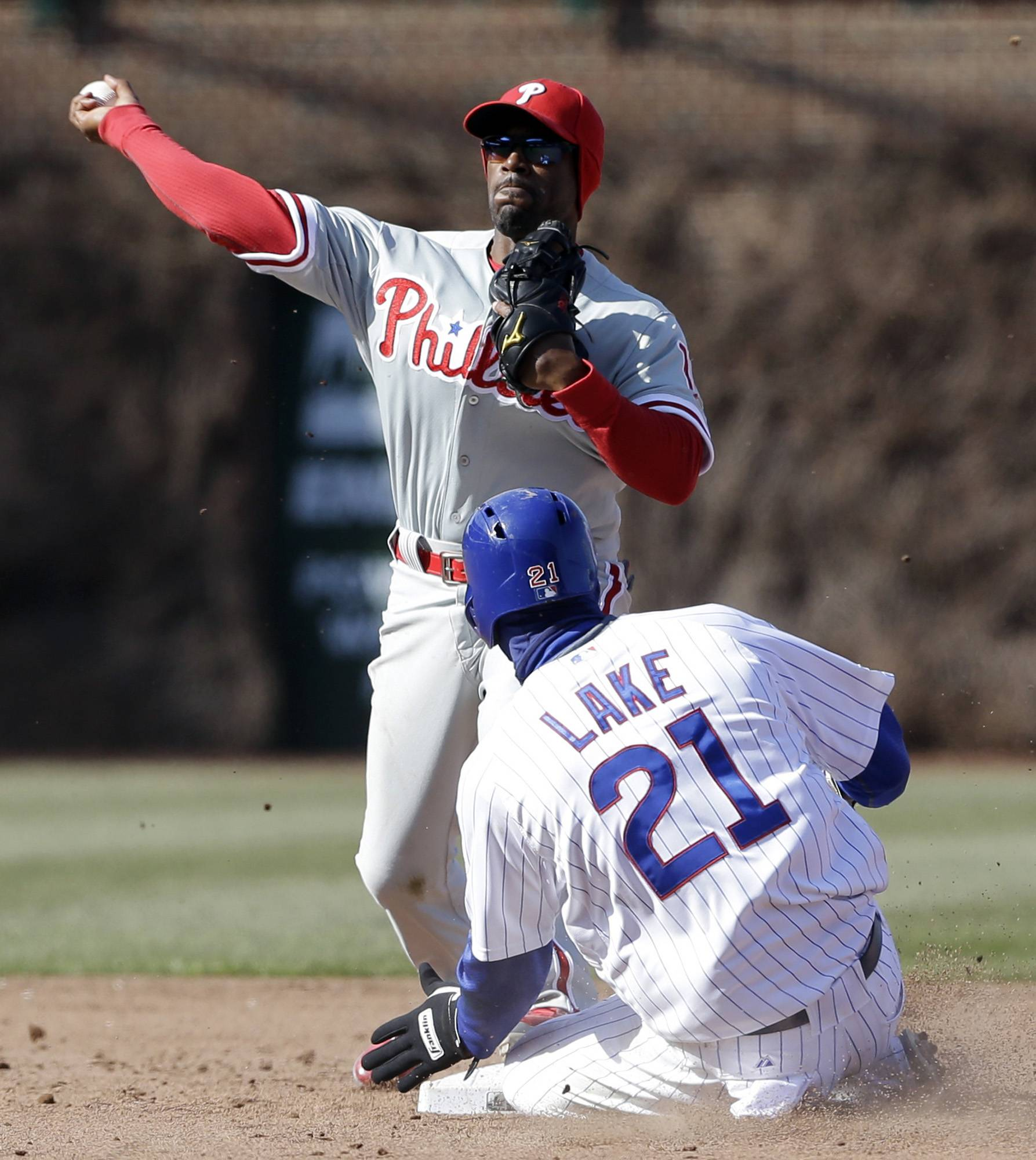 Philadelphia Phillies shortstop Jimmy Rollins, top, throws to first after forcing out Chicago Cubs' Junior Lake during the eighth inning of a baseball game in Chicago, Saturday, April 5, 2014. Chicago Cubs' Mike Olt was safe at first.