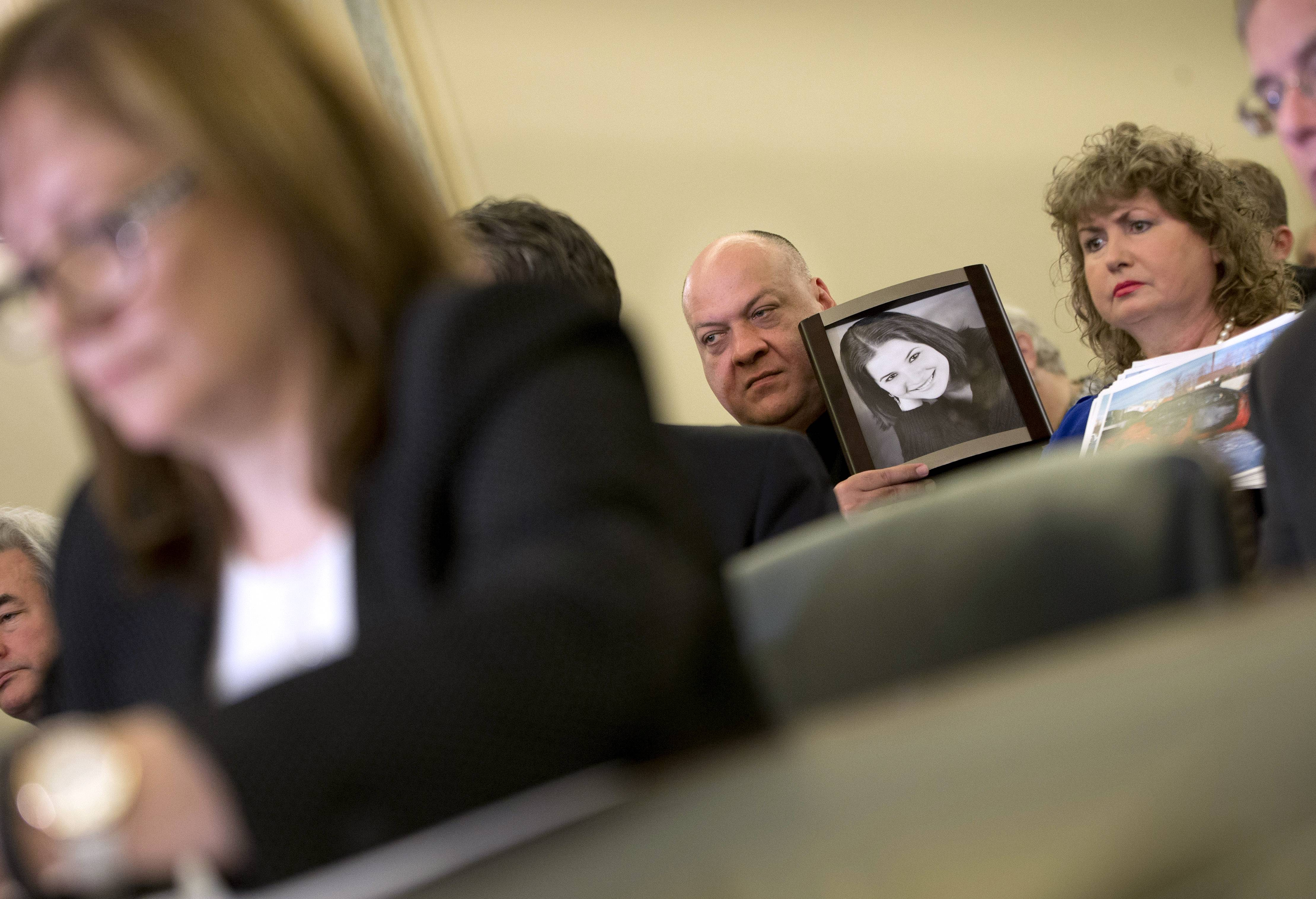 Leo Ruddy, center, and his wife Mary Theresa Ruddy, right, from Scranton, Pa., hold up photographs of their daughter Kelly Erin Ruddy, who died in the crash of a 2005 Chevy Cobalt, as they sit in the audience to listen to testimony by General Motors CEO Mary Barra, left, on Capitol Hill in Washington, Wednesday before the Senate Commerce, Science and Transportation subcommittee.