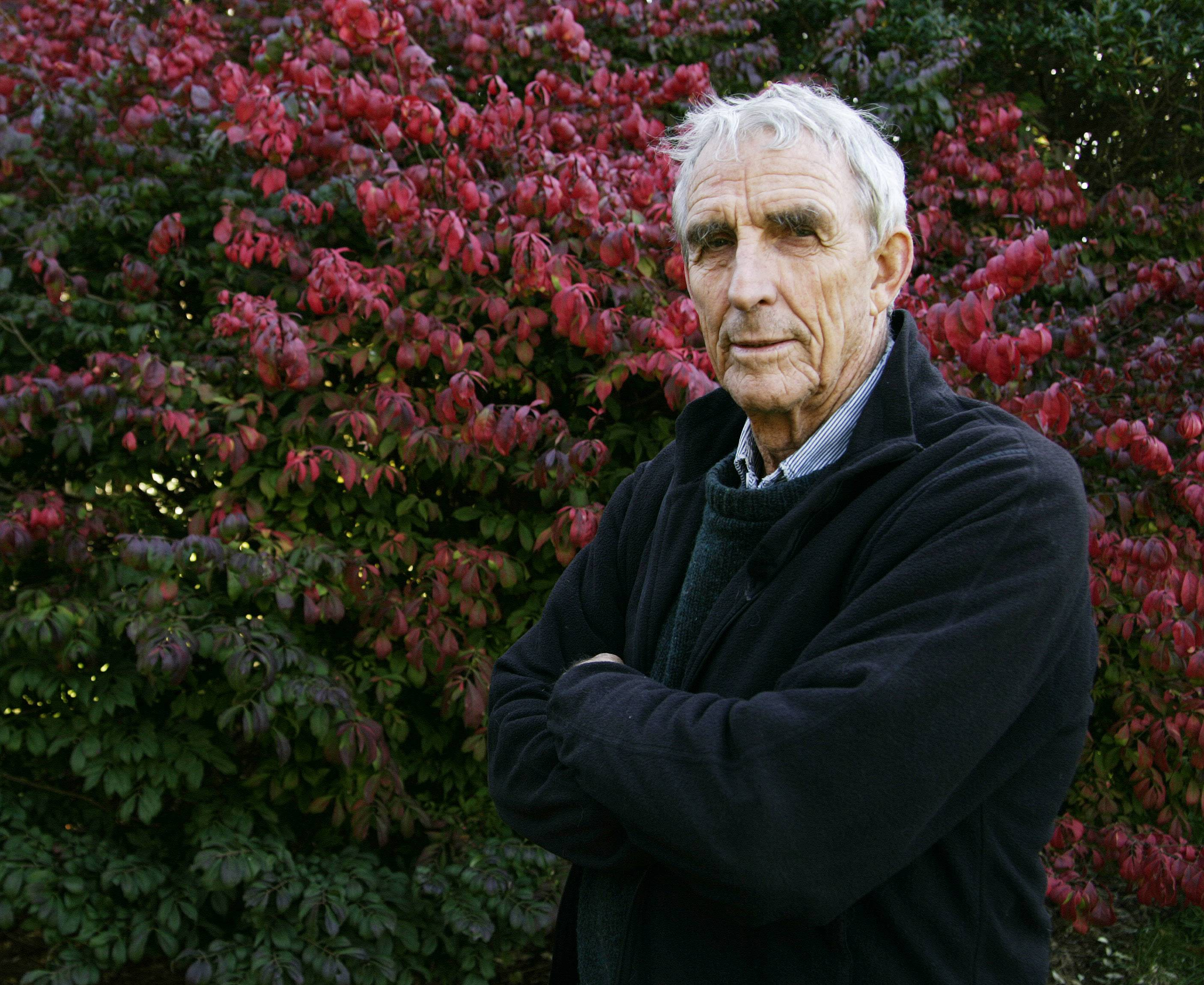 Writer Peter Matthiessen stands in the yard of his house in Sagaponack, N.Y. in this Oct. 28, 2004, file photo. Matthiessen, award-winning author of more than 30 books, world-renowned naturalist, explorer, Buddhist teacher, and political activist, died Saturday.