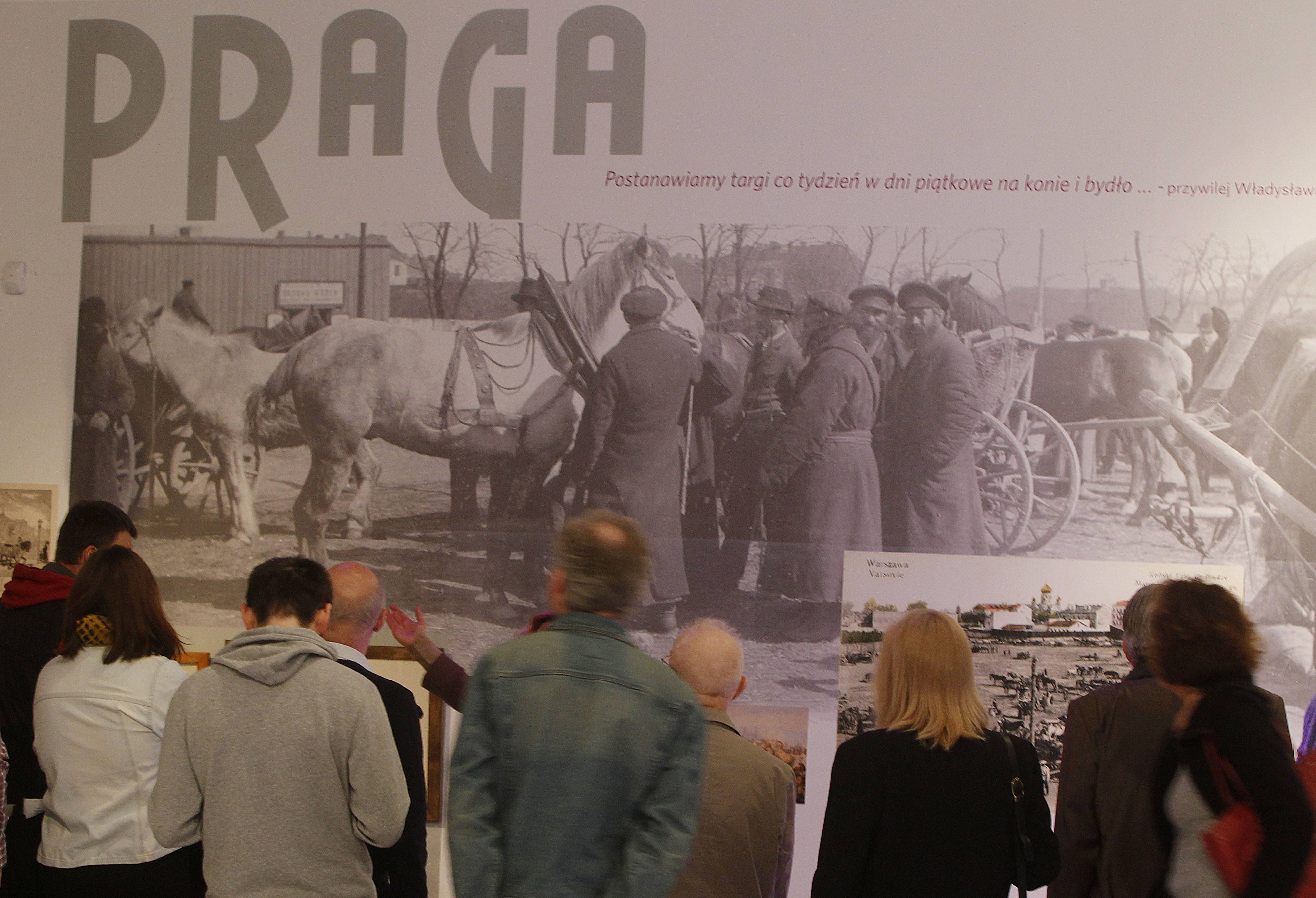 People view a picture of the horse market in pre-World War II Warsaw's Praga district, at a new exhibition by the Museum of the History of Polish Jews, in Warsaw, Poland.