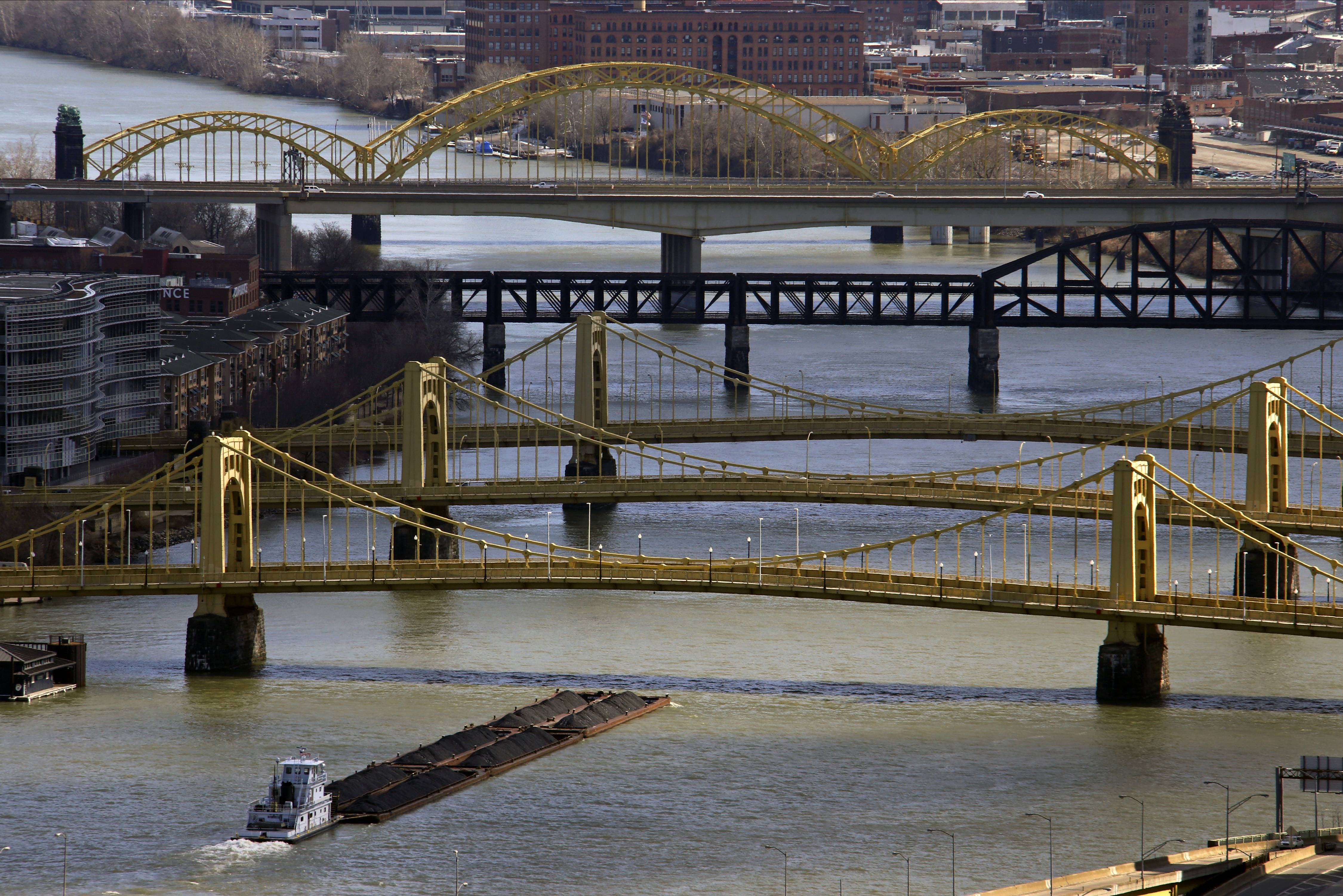 A towboat and barges make their way up the Allegheny River under three historic bridges named after Robert Clemente, foreground, Andy Warhol and Rachel Carson in downtown Pittsburgh.