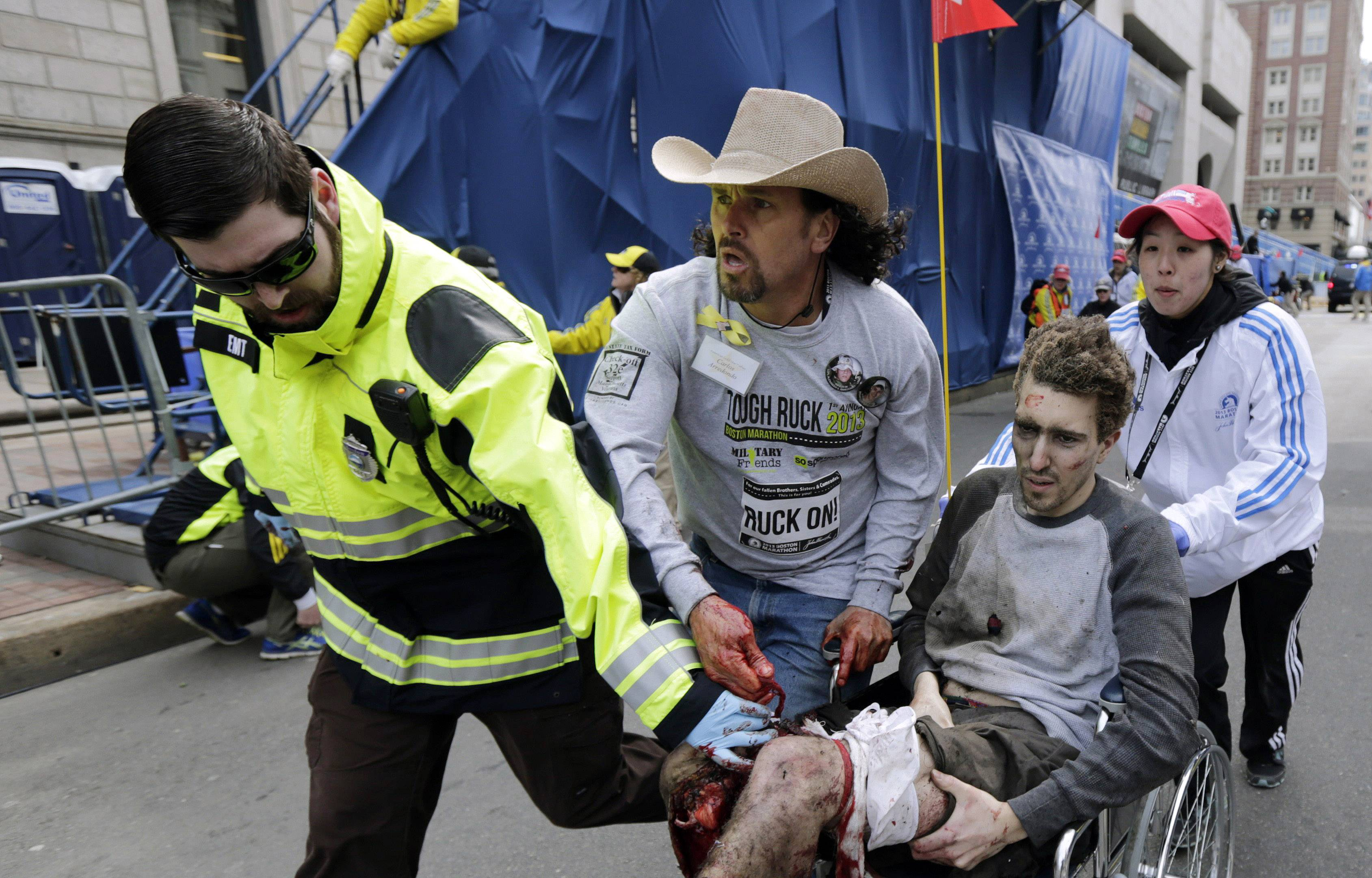 On April 15, 2013, an emergency responder and volunteers, including Carlos Arredondo in the cowboy hat, push Jeff Bauman in a wheelchair after he was injured in an explosion near the finish line of the Boston Marathon in Boston.