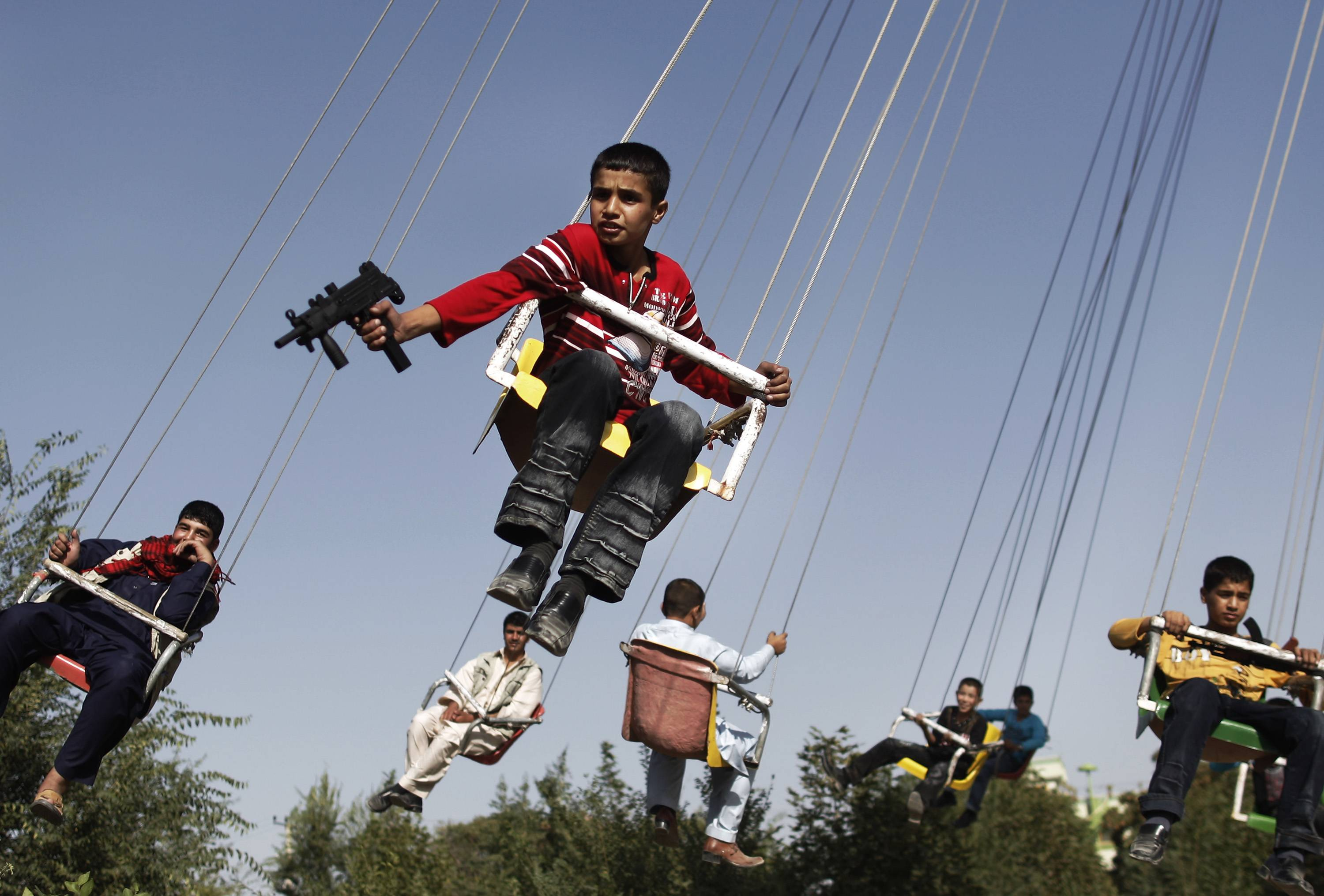 In this Sunday, Sept. 20, 2009 file photo made by Associated Press photographer Anja Niedringhaus, an Afghan boy holds a toy gun as he enjoys a ride with others on a merry-go-round to celebrate the Eid al-Fitr festival, in Kabul, Afghanistan.
