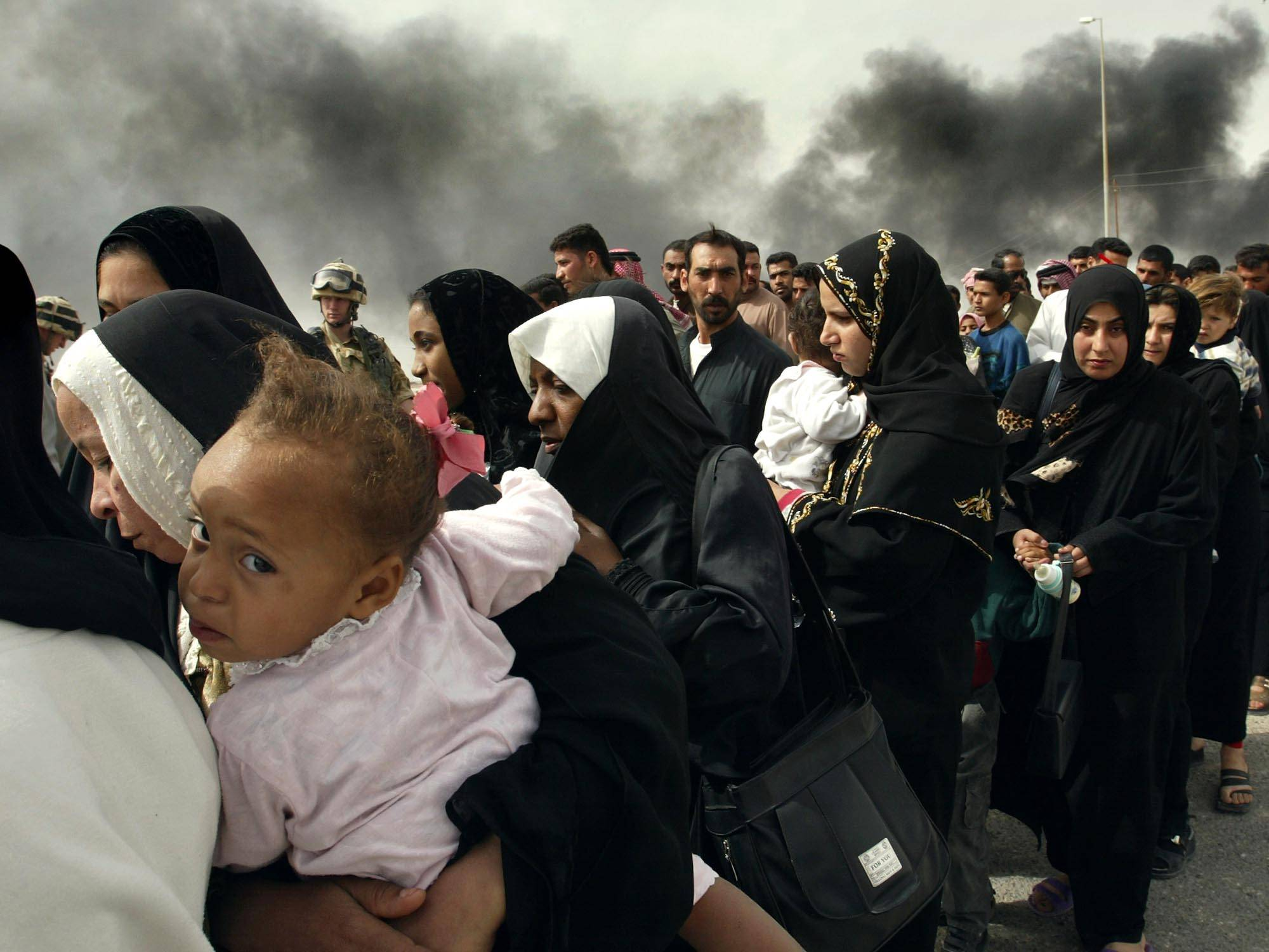 In this Sunday, March 30, 2003 file photo made by Associated Press photographer Anja Niedringhaus, Iraqi women line up for a security check by British soldiers on the outskirts of Basra, as they try to flee from this southern Iraqi town.