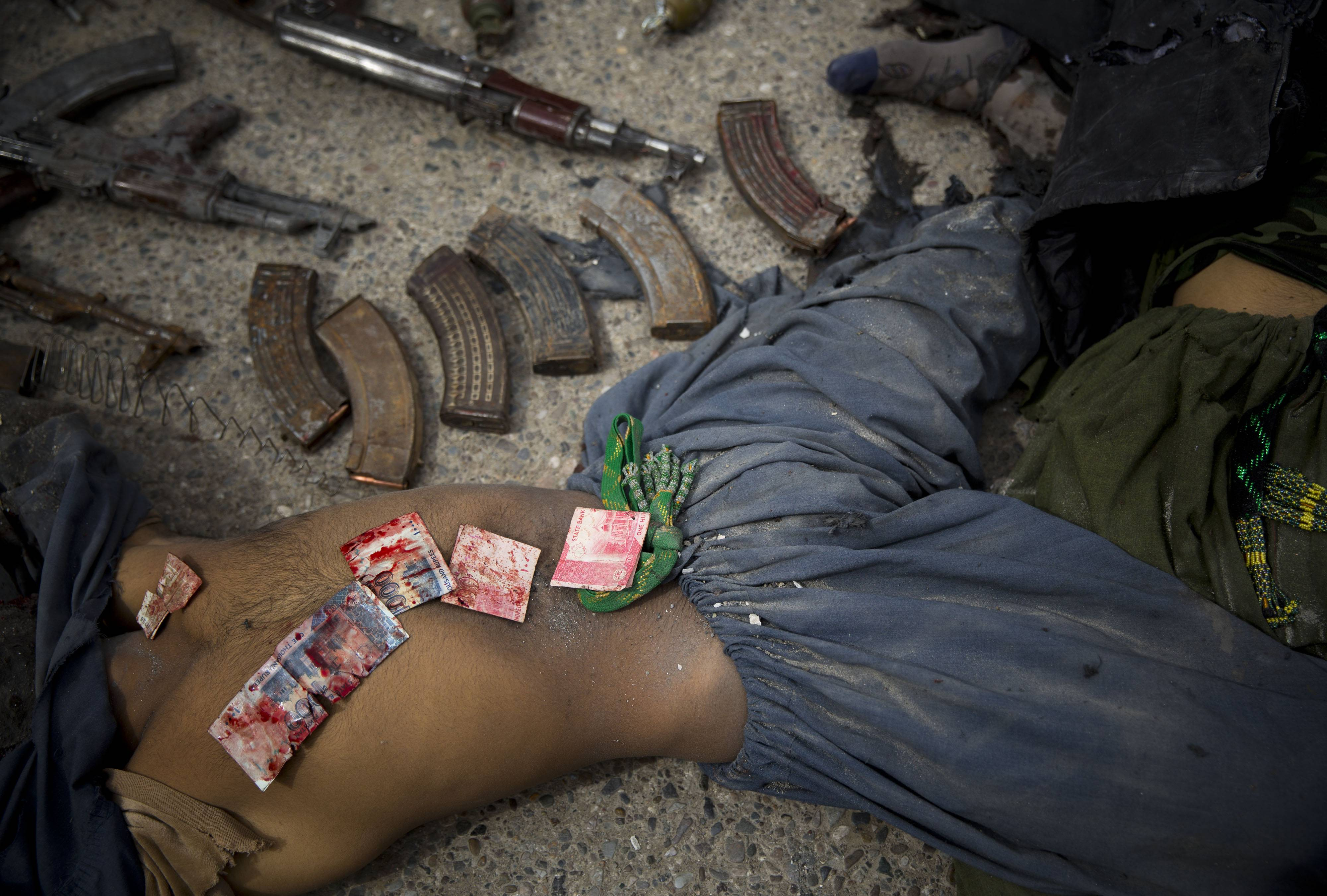 In this Wednesday, March 12, 2014 file photo made by Associated Press photographer Anja Niedringhaus, Pakistani bank notes covered in blood are displayed on the body of a dead suicide bomber after police found them in his pocket after an attack on the former Afghan intelligence headquarters, in the center of Kandahar, Afghanistan.