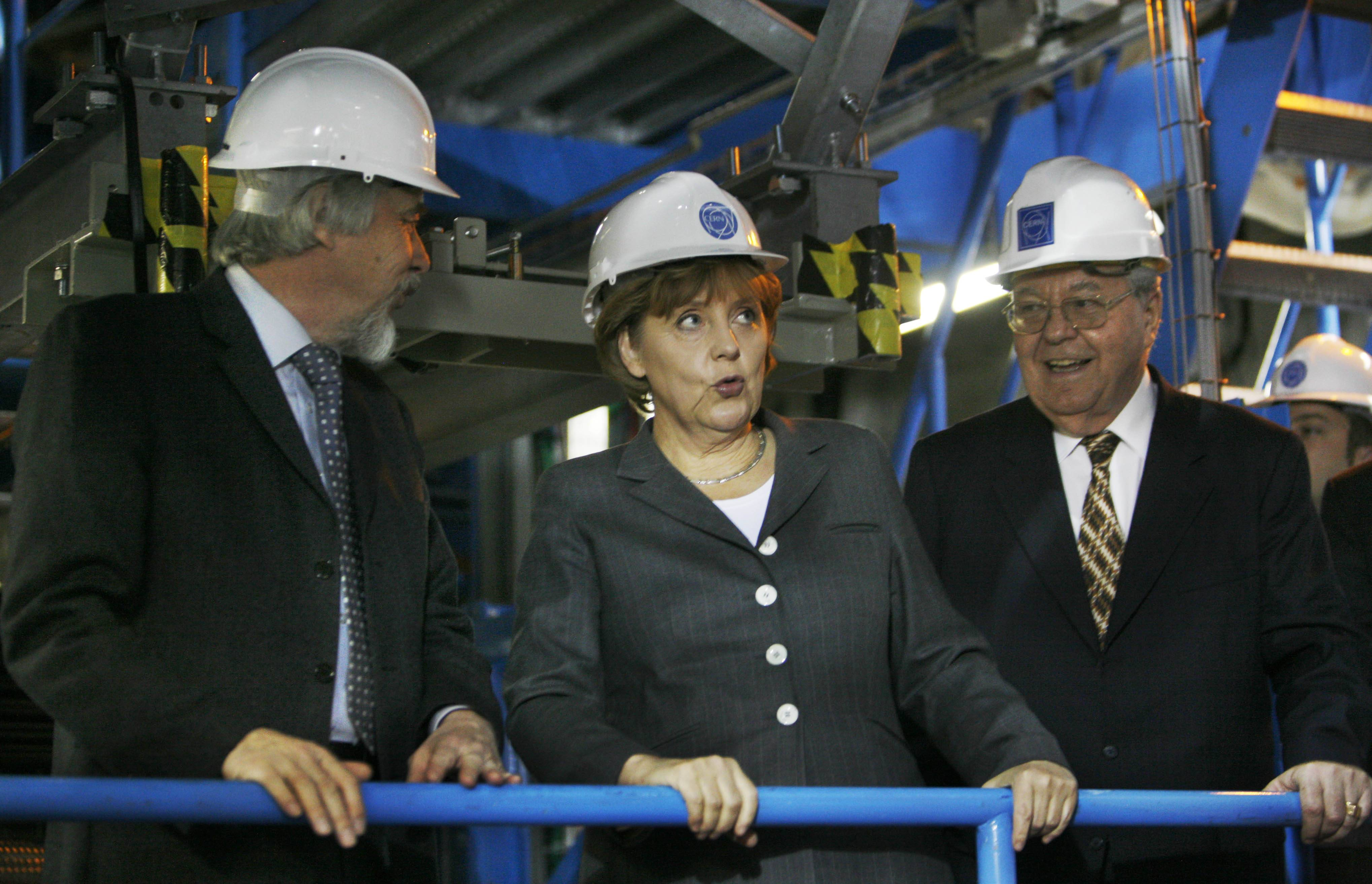 In this Tuesday, April 29, 2008 file photo made by Associated Press photographer Anja Niedringhaus, German chancellor Angela Merkel, center, grimaces, as she tours CERN, the European Organization for Nuclear Research, with Rolf Heuer, CERN Director designated, left, and Robert Aymar, Director General CERN, in Geneva, Switzerland.