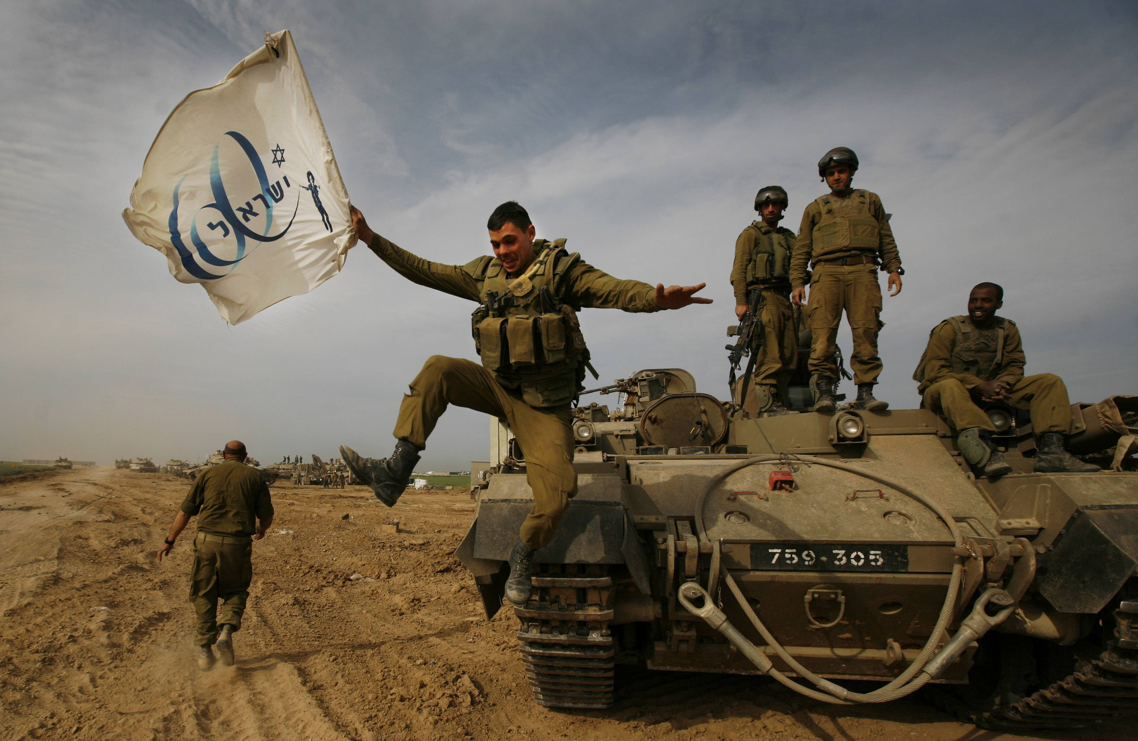 In this Friday, Jan. 16, 2009 file photo made by Associated Press photographer Anja Niedringhaus, an Israeli soldier jumps off an armored vehicle carrying a flag of Israel's 60th anniversary as he celebrates with his unit their return from the Gaza Strip on the Israeli side of the border.