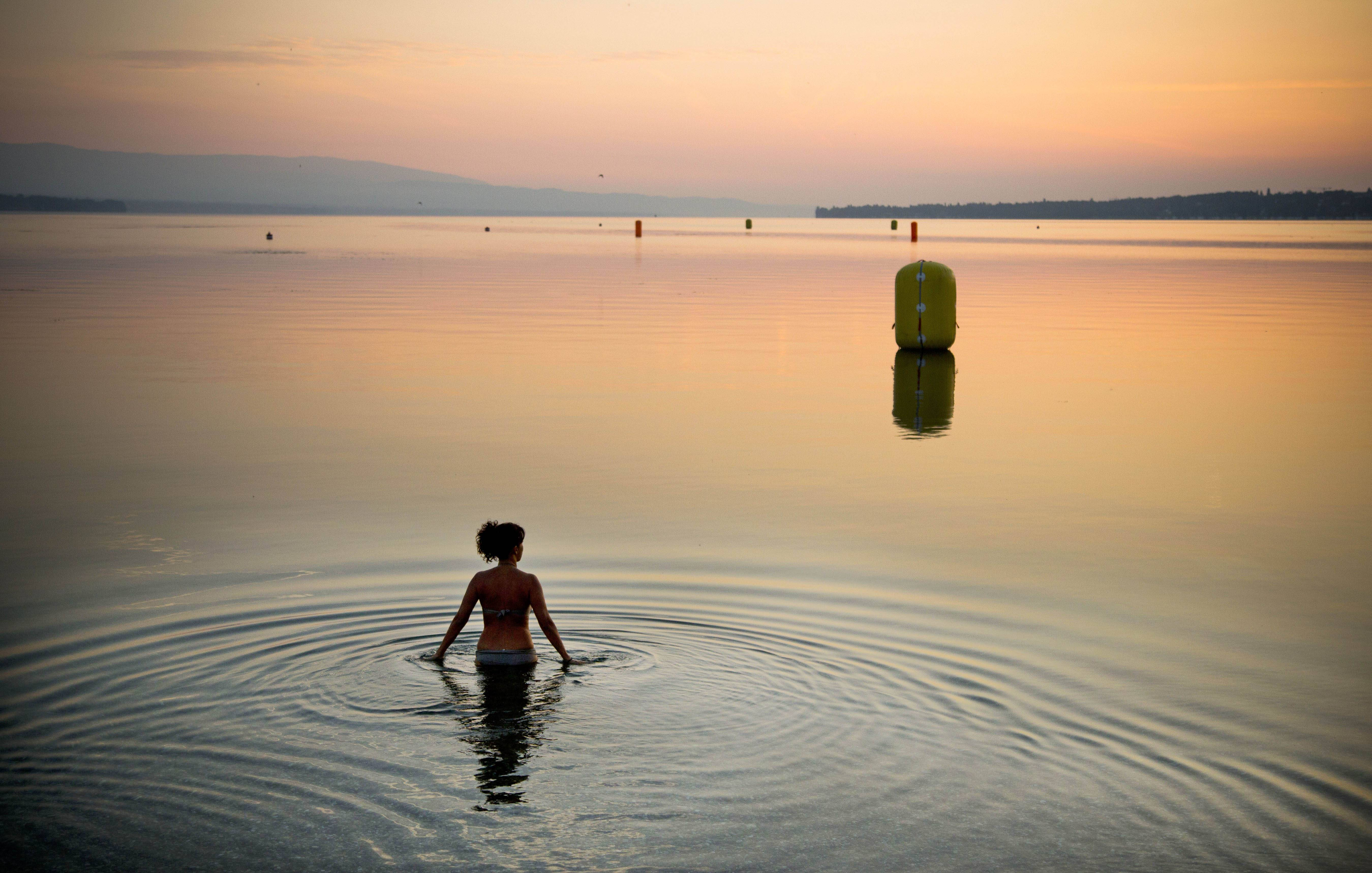 In this Sunday, July 21, 2013 file photo made by Associated Press photographer Anja Niedringhaus, a woman takes a dip in Lake Geneva at sunrise in Geneva, Switzerland.