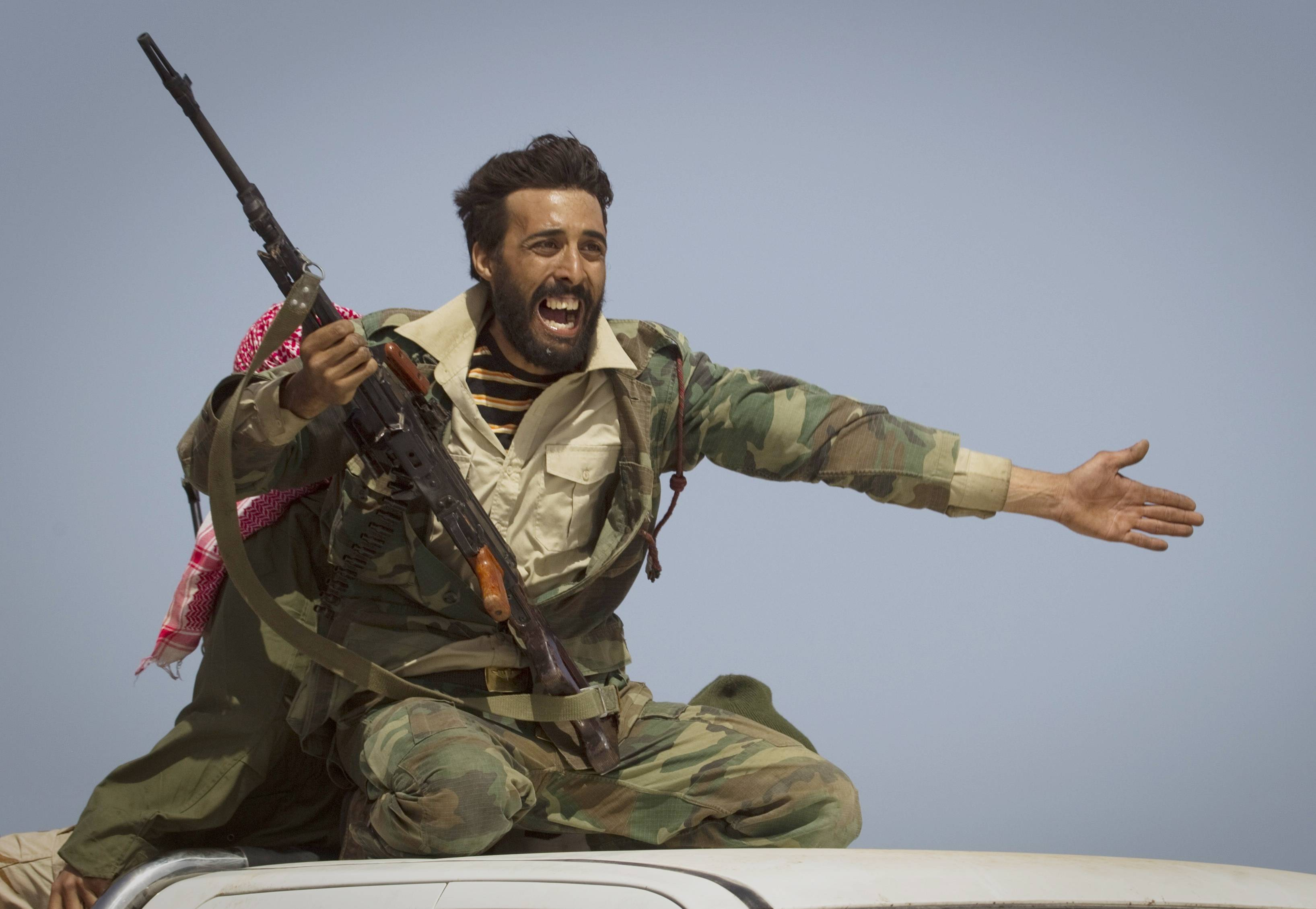 In this March 29, 2011 file photo made by Associated Press photographer Anja Niedringhaus, a Libyan rebel urges people to leave as shelling from Gadhafi's forces started landing on the front line outside of Bin Jawaad, 150 kilometers (93 miles) east of Sirte, central Libya.