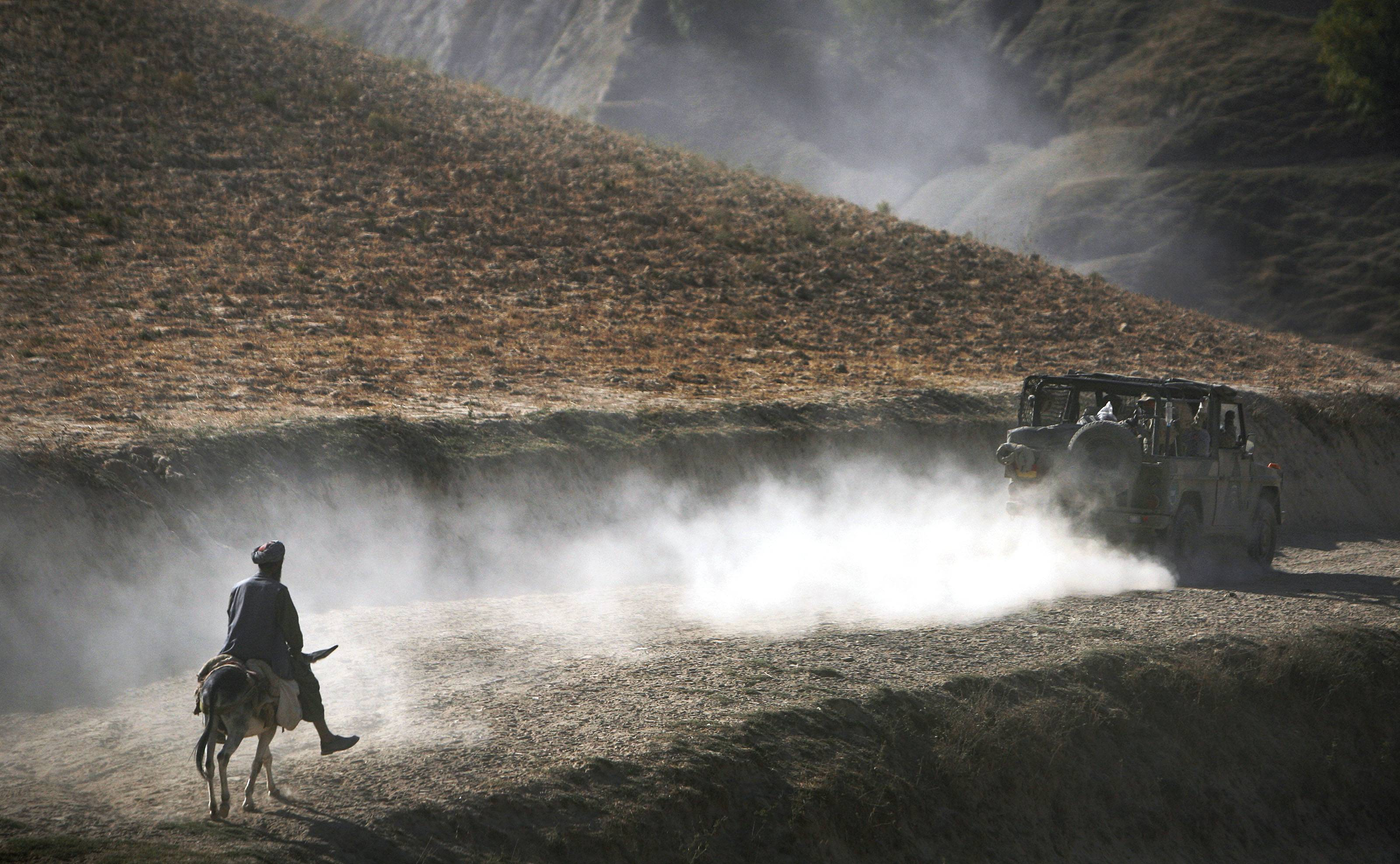 In this Tuesday, Sept. 15, 2009 file photo made by Associated Press photographer Anja Niedringhaus, an Afghan man on his donkey follows a convoy of German ISAF soldiers patrolling Yaftal E Sofla, in the mountainous region of Feyzabad, east of Kunduz, Afghanistan.