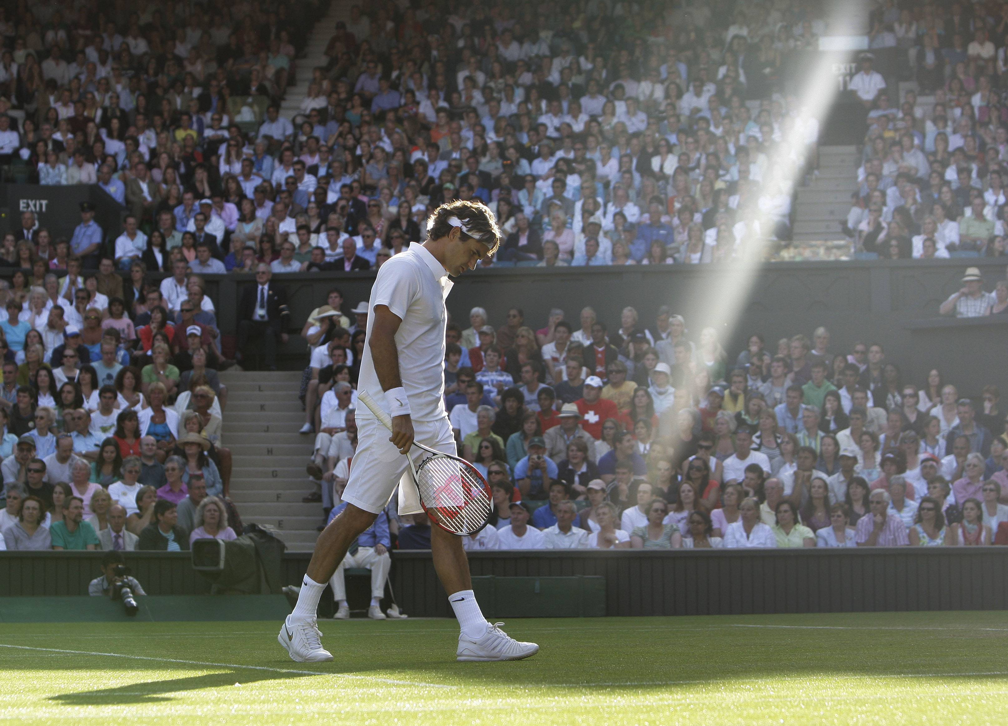 In this Wednesday, June 25, 2008 file photo made by Associated Press photographer Anja Niedringhaus, Switzerland's Roger Federer walks across the court as a shaft of late afternoon light illuminates the Centre Court during his second round match against Sweden's Robin Soderling at Wimbledon, England.