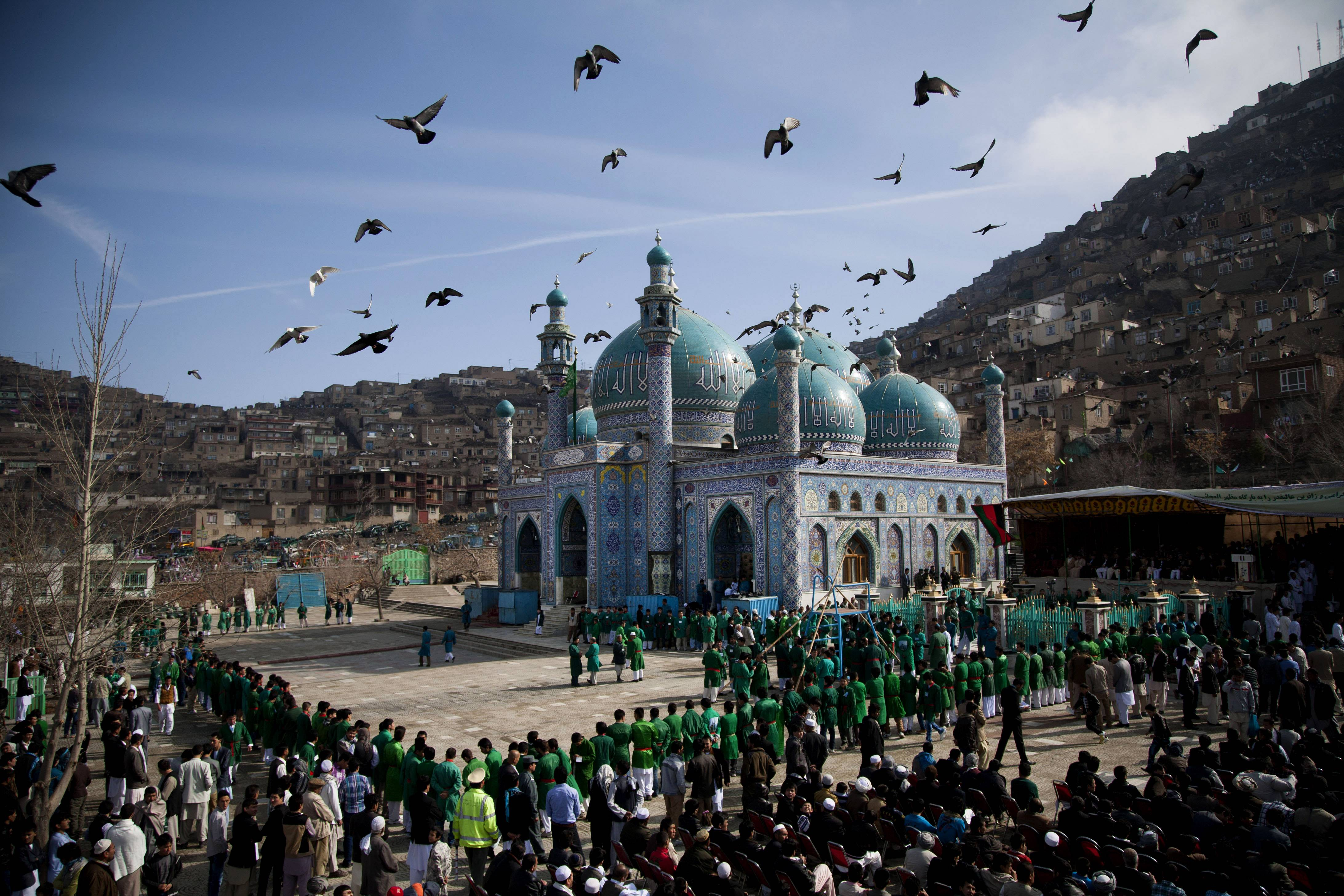 In this Thursday, March 21, 2013 file photo made by Associated Press photographer Anja Niedringhaus, hundreds of Afghans wait to see the holy flag at the Kart-e Sakhi mosque in Kabul, Afghanistan.