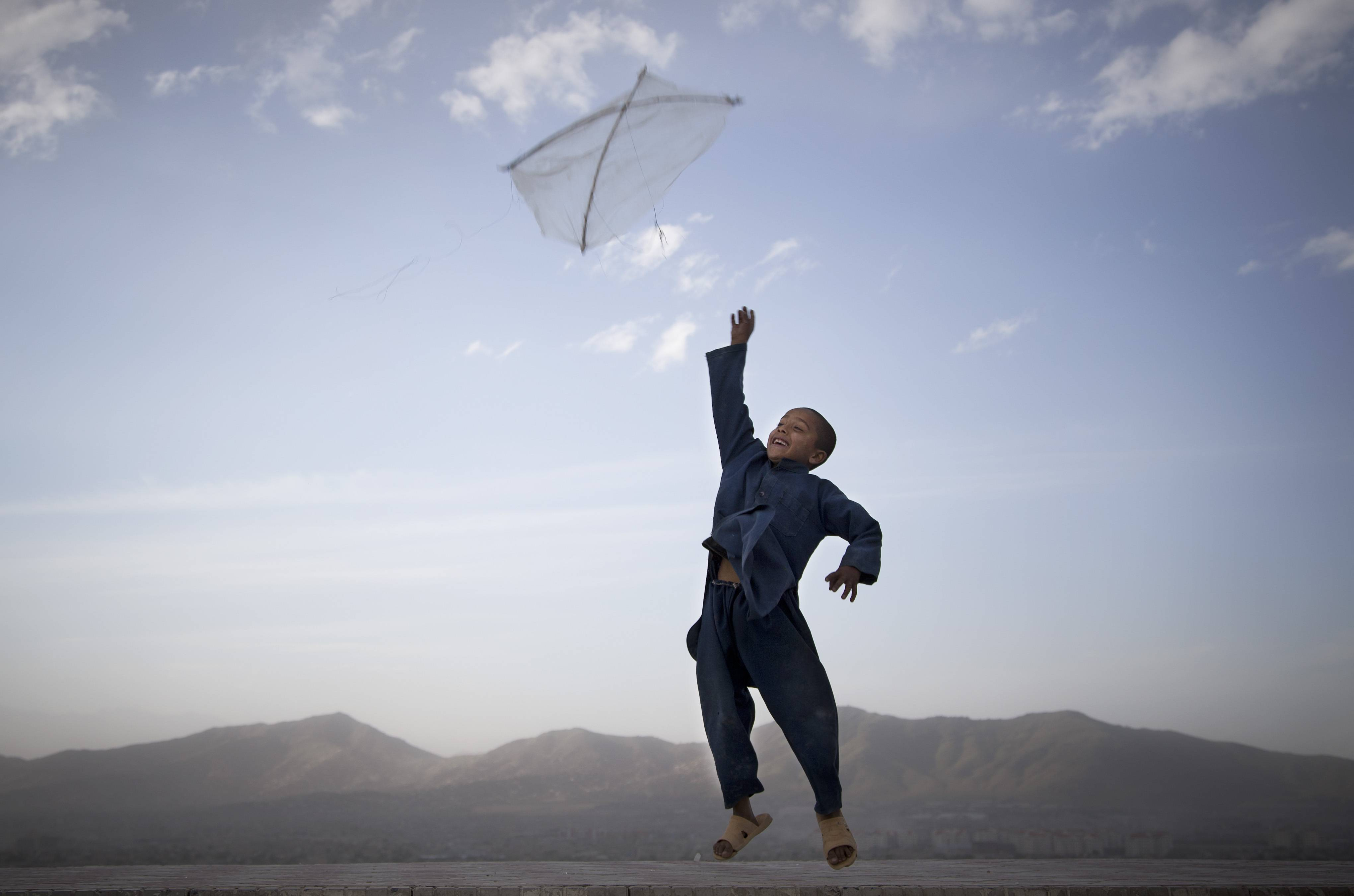 In this May 13, 2013 file photo made by Associated Press photographer Anja Niedringhaus, an Afghan boy flies his kite on a hill overlooking Kabul, Afghanistan. =