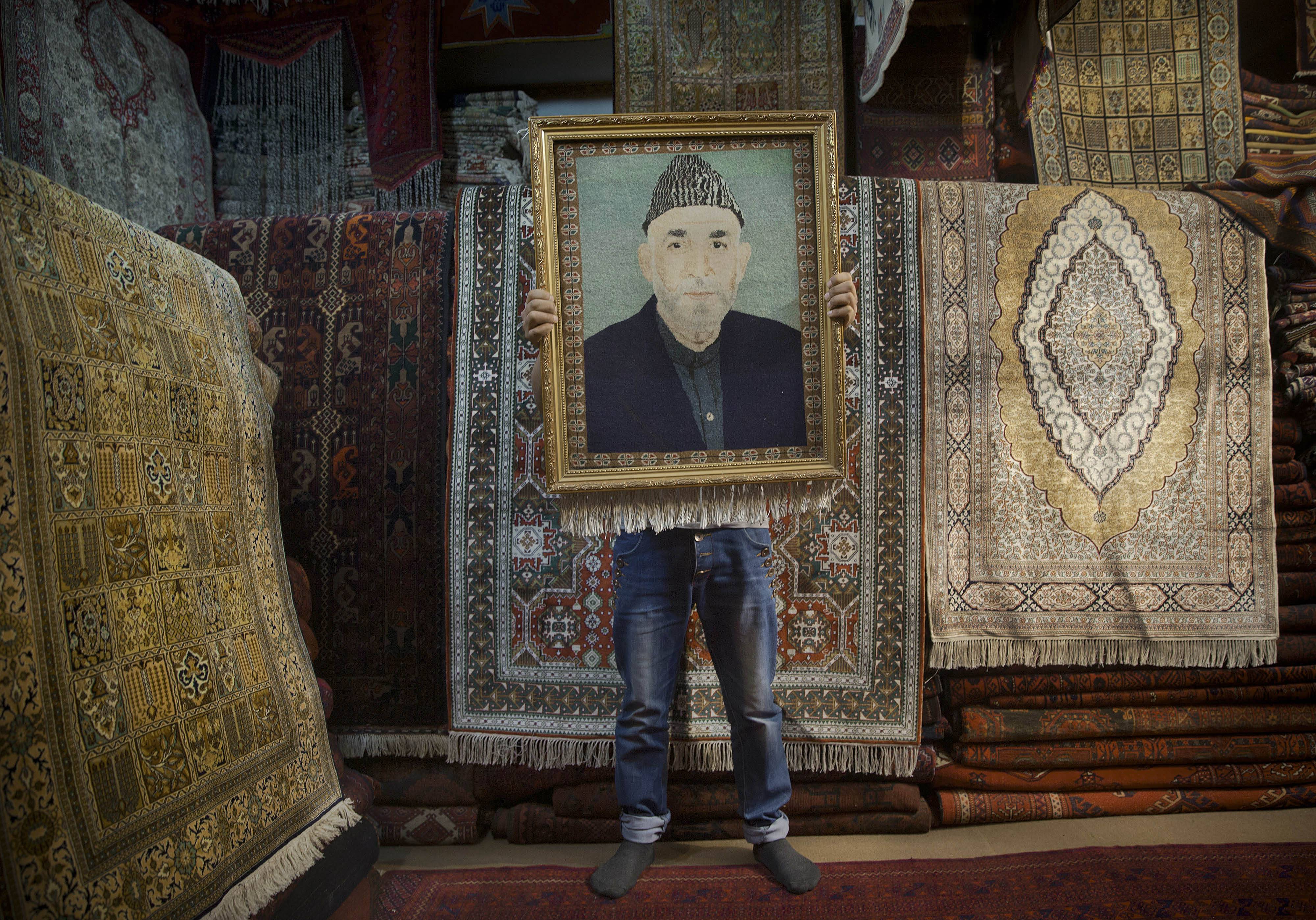 In this Sunday, March 30, 2014 file photo made by Associated Press photographer Anja Niedringhaus, an Afghan carpet seller holds up a framed carpet depicting Afghan President Hamid Karzai in his store in Kabul, Afghanistan.