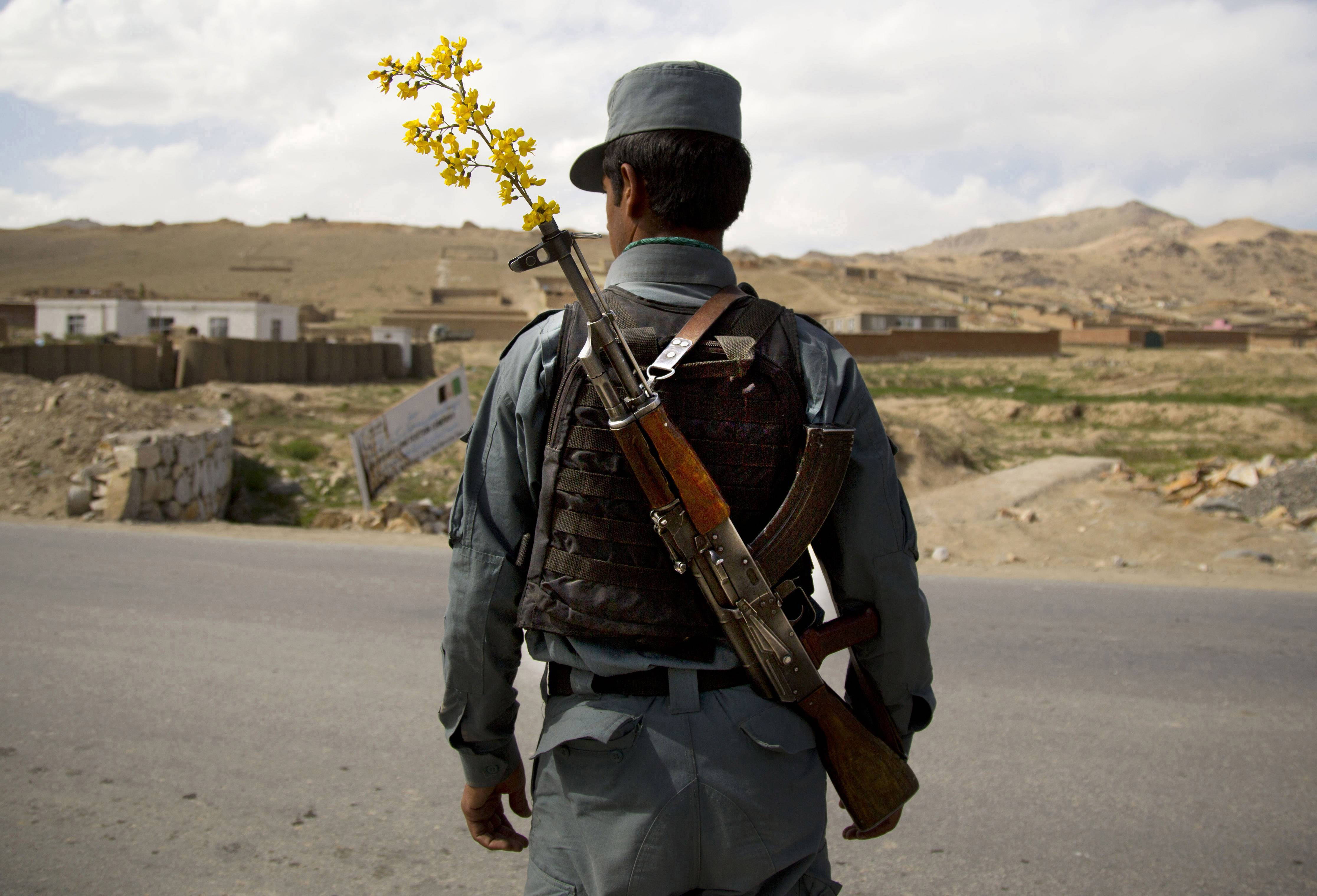 In this Wednesday, May 15, 2013 file photo made by Associated Press photographer Anja Niedringhaus, an Afghan National Police officer mans a checkpoint in the outskirts of Maydan Shahr, Wardak province, Afghanistan.
