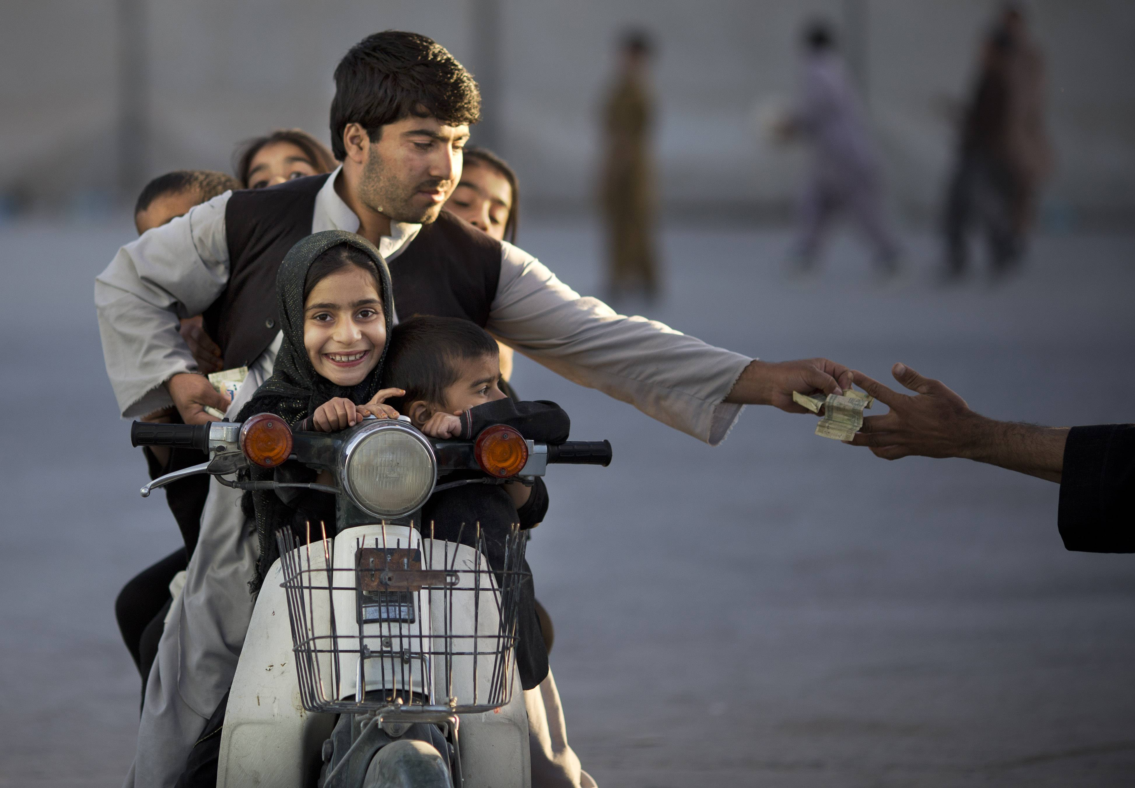 In this Friday, Nov. 1, 2013 file photo made by Associated Press photographer Anja Niedringhaus, an Afghan man with his five children on his motorbike pays money to enter a park in Kandahar, southern Afghanistan.
