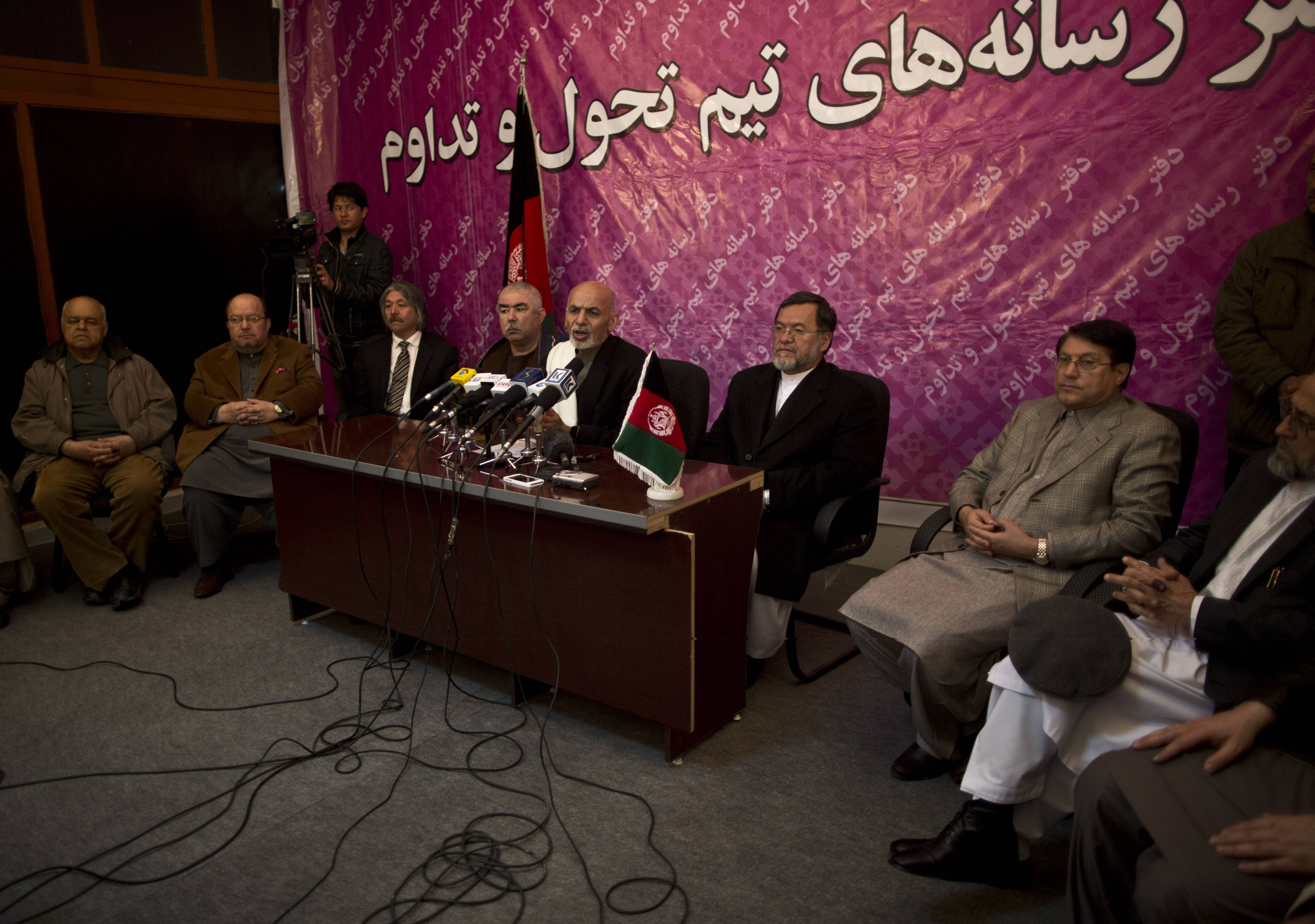 Afghan presidential candidate Ashraf Ghani Ahmadzai, center, surrounded by party members, speaks during a news conference, in Kabul, Afghanistan, Saturday.